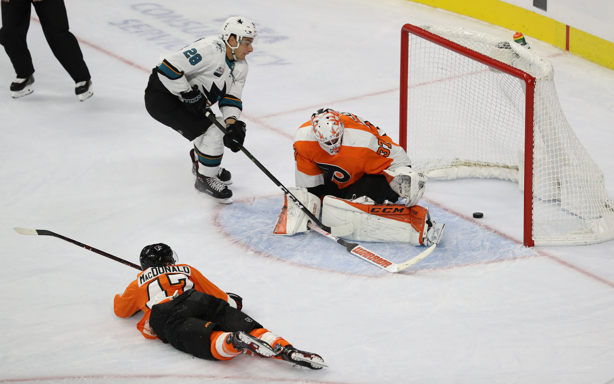 Timo Meier, center, of the Sharks scores between the legs of Brian Elliott, right, of the Flyers.  Andrew MacDonald is left. The Flyers take the ice in their home opener against the Sharks on Oct. 9, 2018.    CHARLES FOX / Staff Photographer