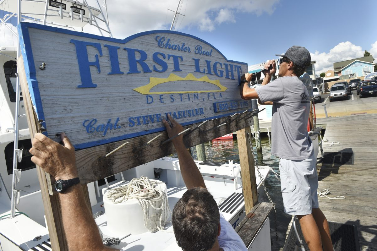 """Capt. Steve Haeusler, left, and Wyatt Ferreira take down the sign for Haeusler�s charter fishing boat """"First Light"""" on Monday. Boat captains are relocating their vessels to safer locations in advance of Hurricane Michael."""