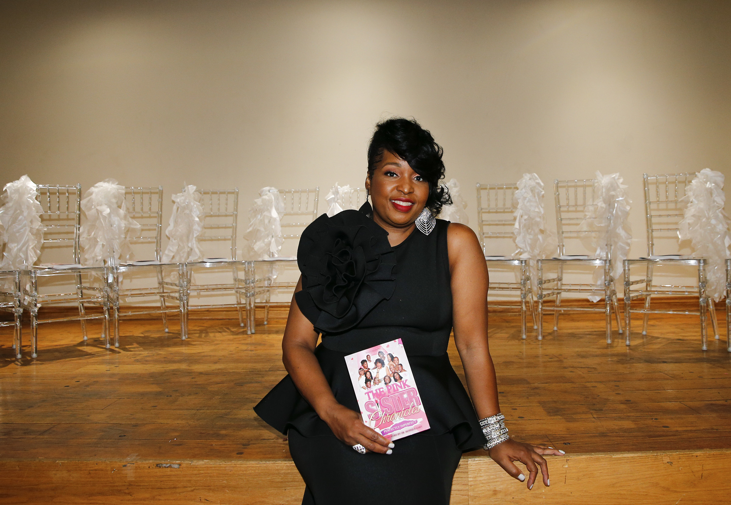 Traci Smith holds a copy of The Pink Sister Chronicles Perfectly Imperfect Volume 4 during a book signing/gala at the African American Museum in Philadelphia on Oct. 4, 2018.