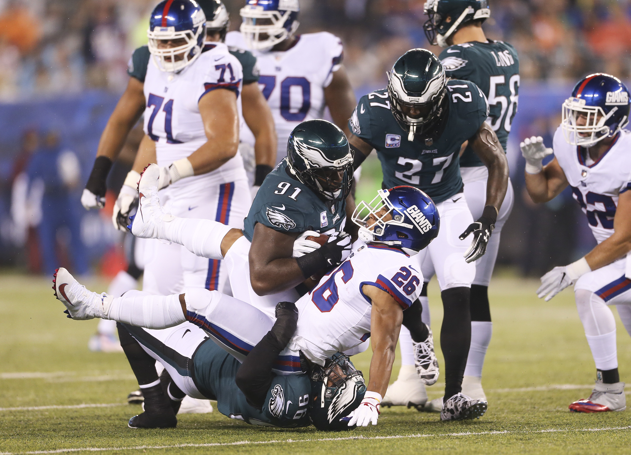 Eagles defensive end Derek Barnett, defensive tackle Fletcher Cox (91) and strong safety Malcolm Jenkins (27) stop Giants running back Saquon Barkley in the first quarter.