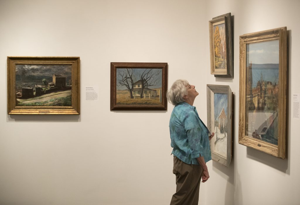 A visitor examines an exhibit of local school districts' art collections at the James A. Michener Museum. The exhibit includes 15 paintings from the Philadelphia School District.