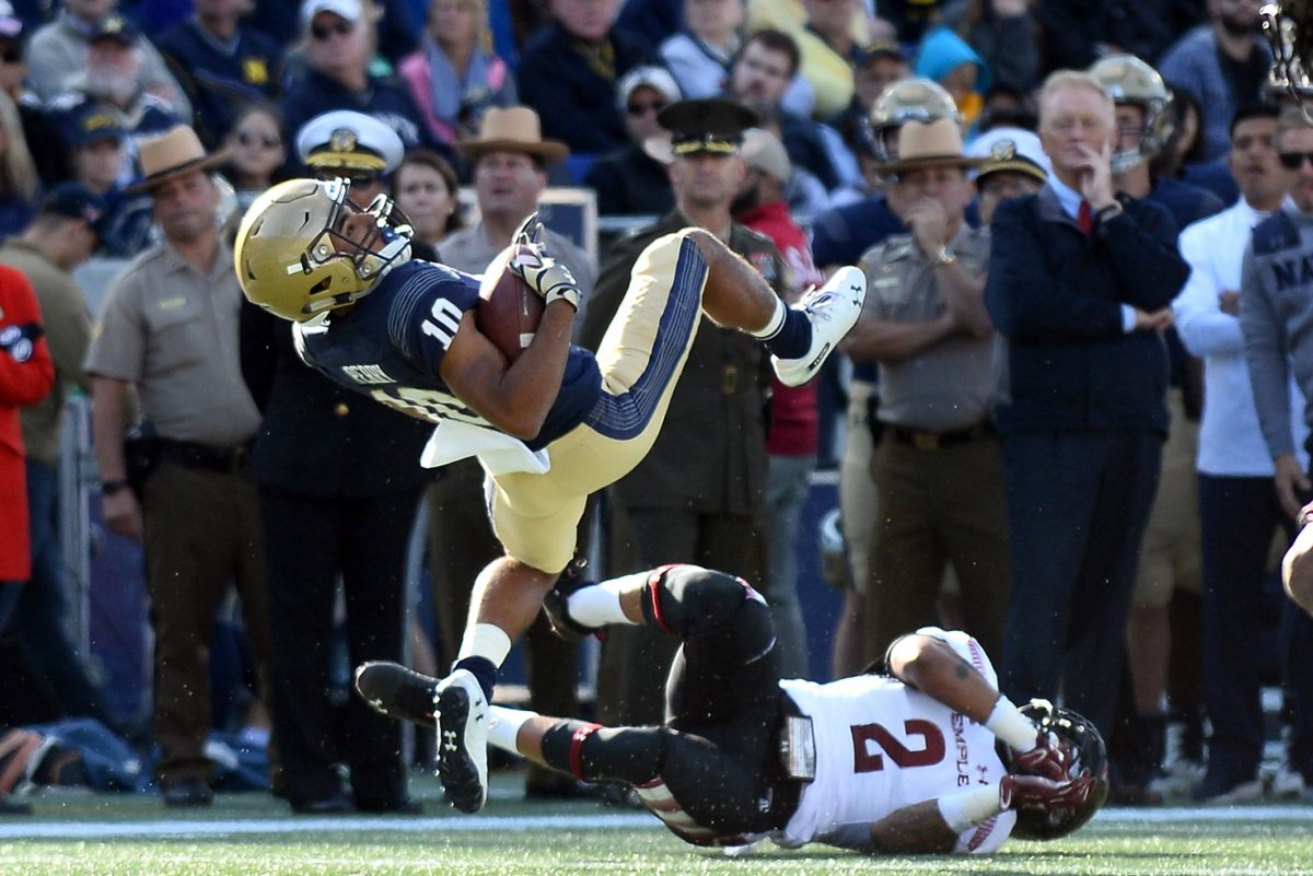 Navy's Malcolm Perry is flipped by Temple's Delvon Randall (2) on a run in the first quarter at Navy-Marine Corps Memorial Stadium in Annapolis, Md., on Saturday, Oct. 13, 2018. Temple won, 24-17.