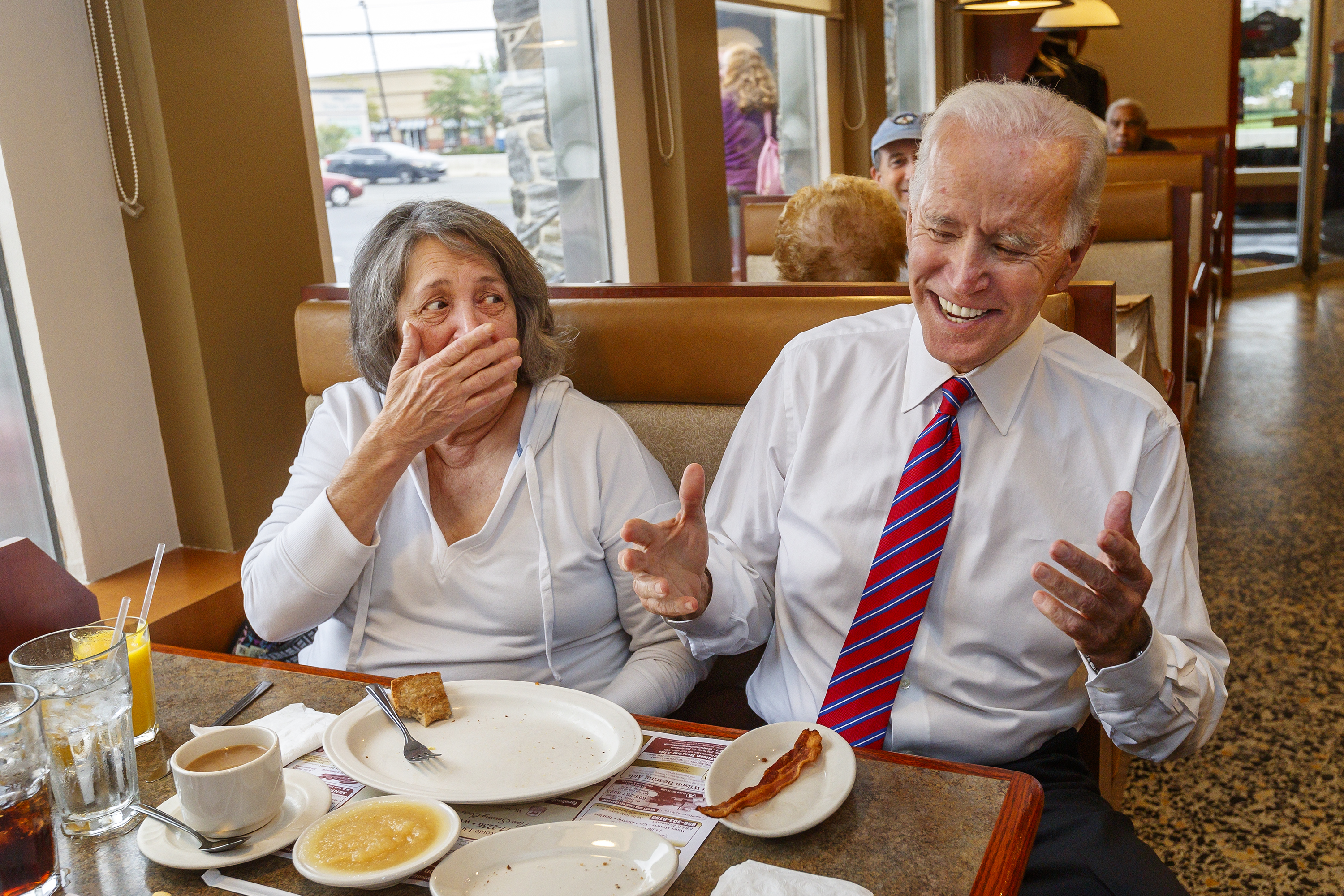 Former vice president Joe Biden, right, makes Phyllis Ponisciak, left, laugh as he visits with her and her husband, Joe, in the Golden Dawn Diner in Willingsboro, NJ, as he campaigns for Andy Kim, who´s locked in a tight race for a Congressional seat against incumbent Tom MacArthur