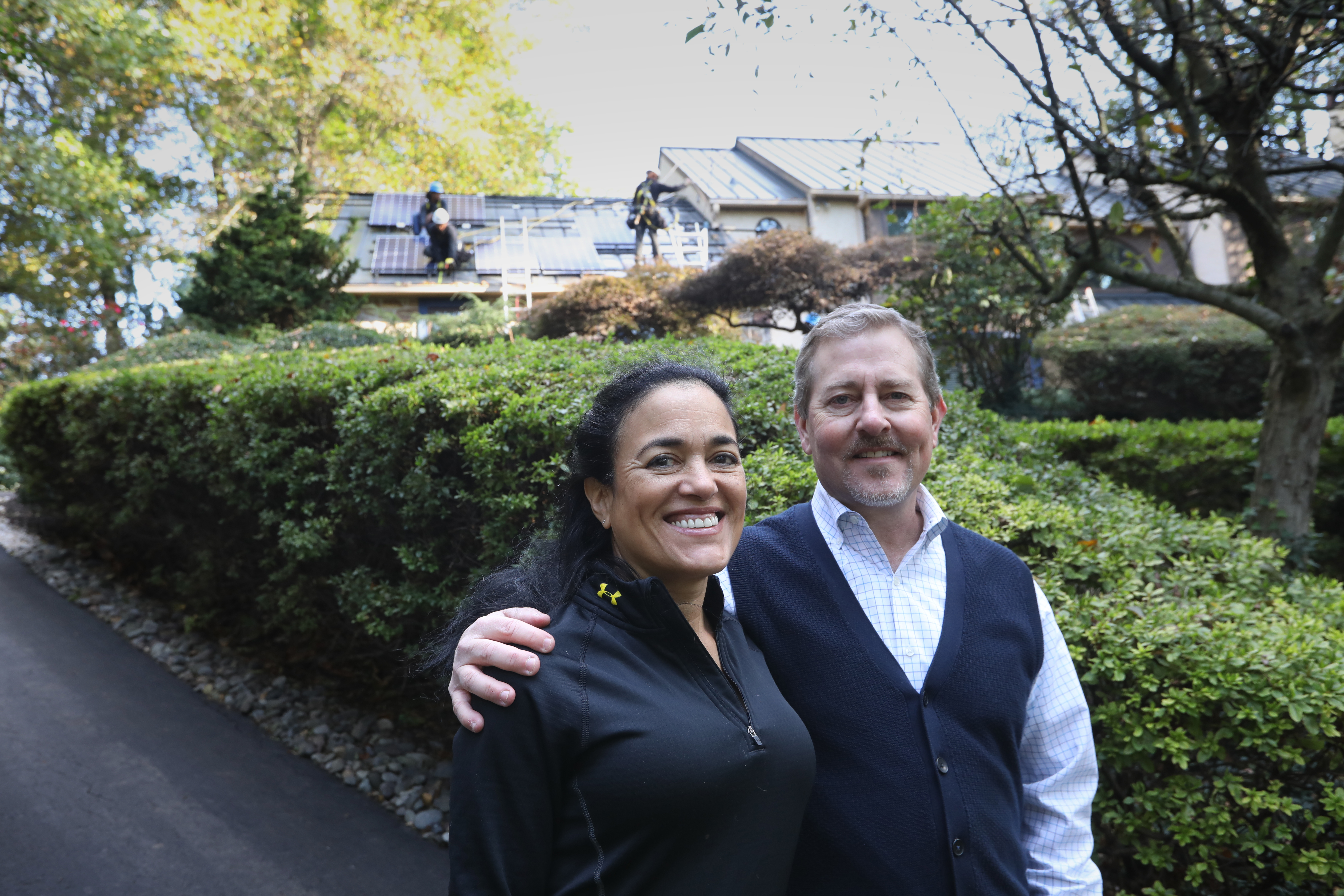 Yolanda and Bill Hopping stand outside their Birmingham Township home as a work crew installs a rooftop solar system.