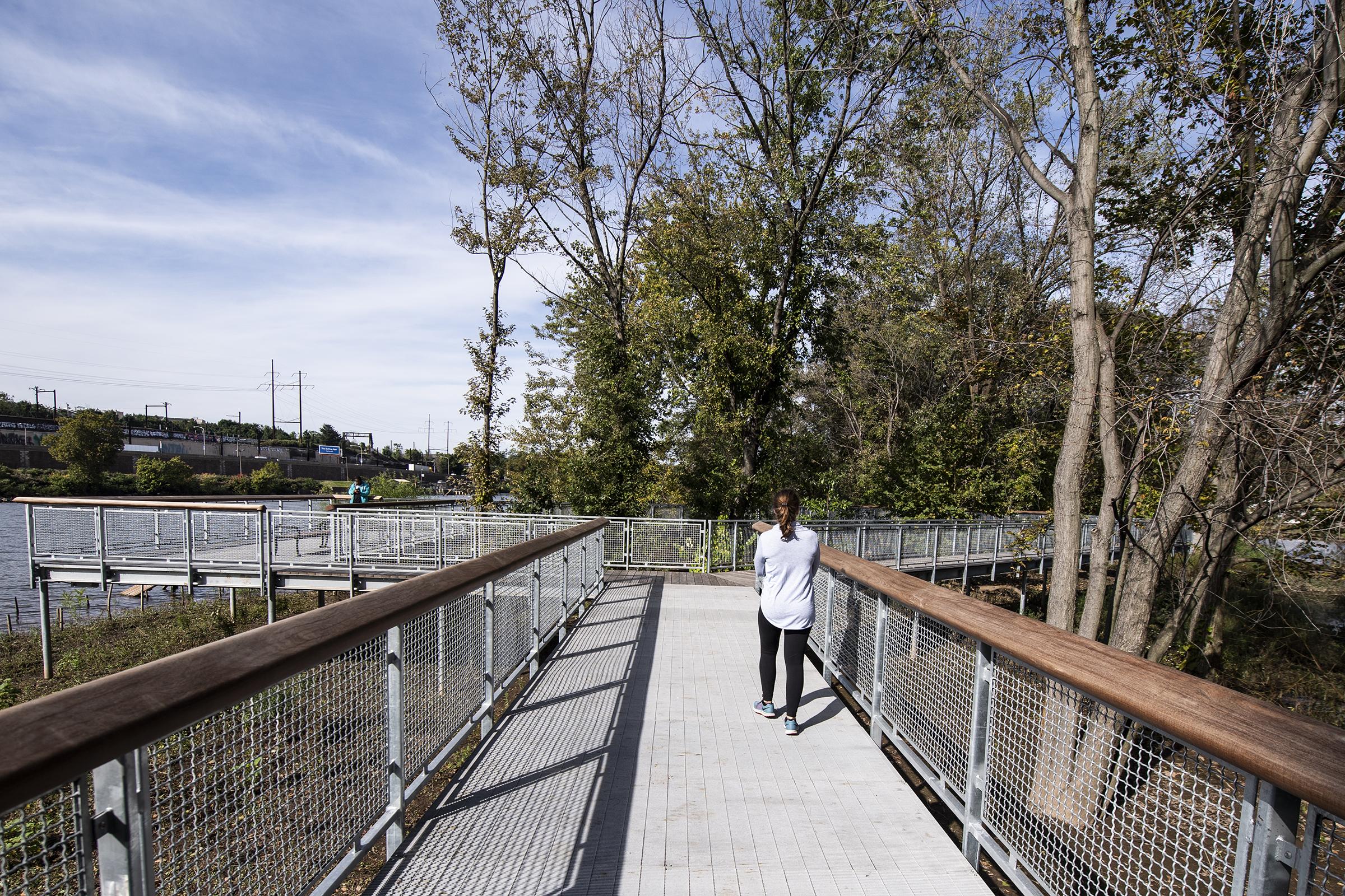 A woman walks on the bridge of the Philadelphia Parks & RecreationÕs Fairmount Water Works Boardwalk and Trail at Boathouse Row, Philadelphia, PA. Tuesday, October 16, 2018. JOSE F. MORENO / Staff Photographer.
