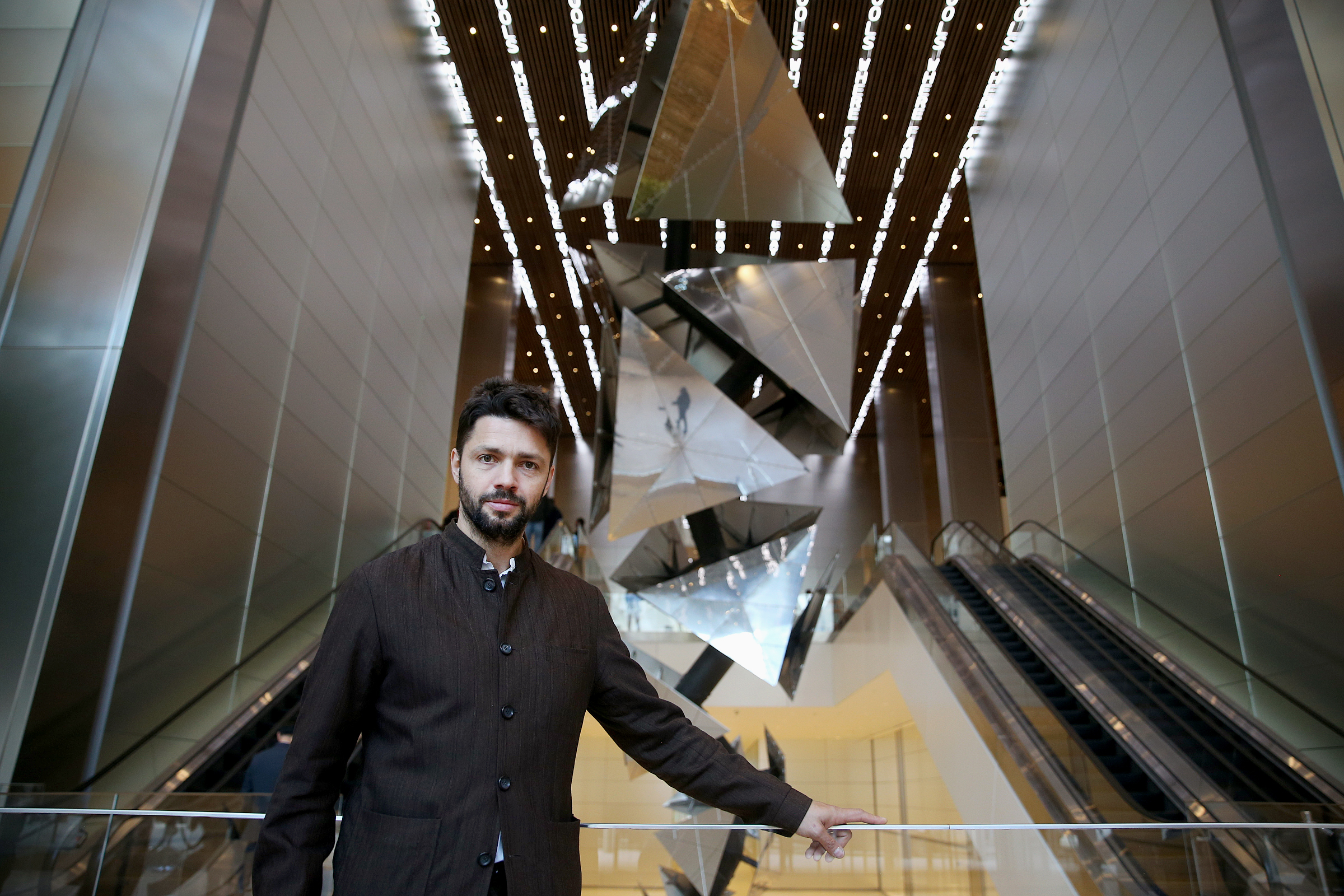 "Artist Conrad Shawcross stands for a portrait in front of his work ""Exploded Paradigm"" in the lobby of the new Comcast Technology Center in Center City Philadelphia on Wednesday, Oct. 17, 2018. The newly completed skyscraper is the city´s tallest."