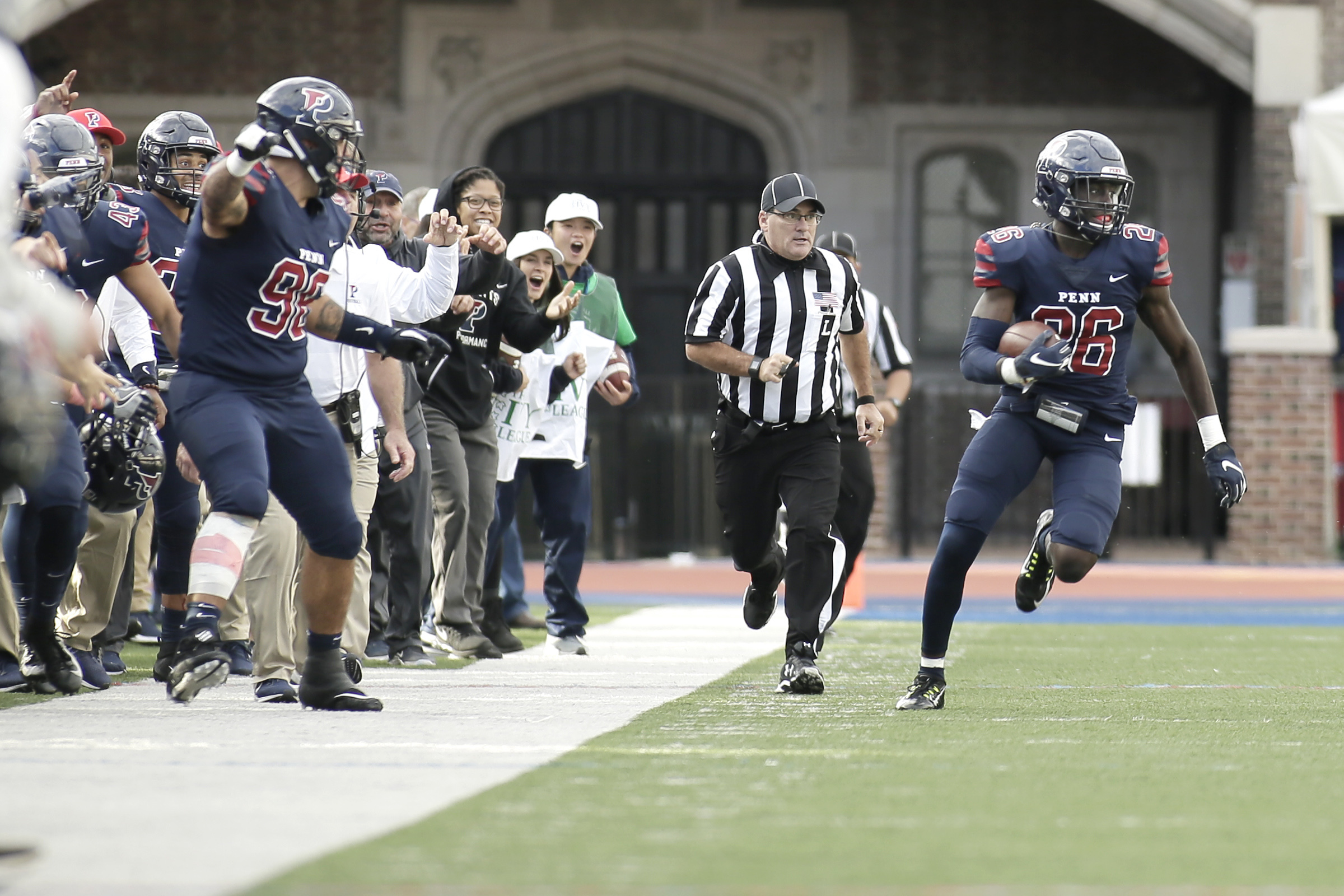 With teammates and supporters on the sidelines pointing which direction to run, Penn's # 26 Mohammed Diakite runs back his late 4th quarter interception during the Columbia at University of Penn football game at Franklin Field in Phila., Pa. on October 13, 2018. The interception preserved Penn's lead with only 7 seconds to go and Penn won the game 13-10. ELIZABETH ROBERTSON / Staff Photographer