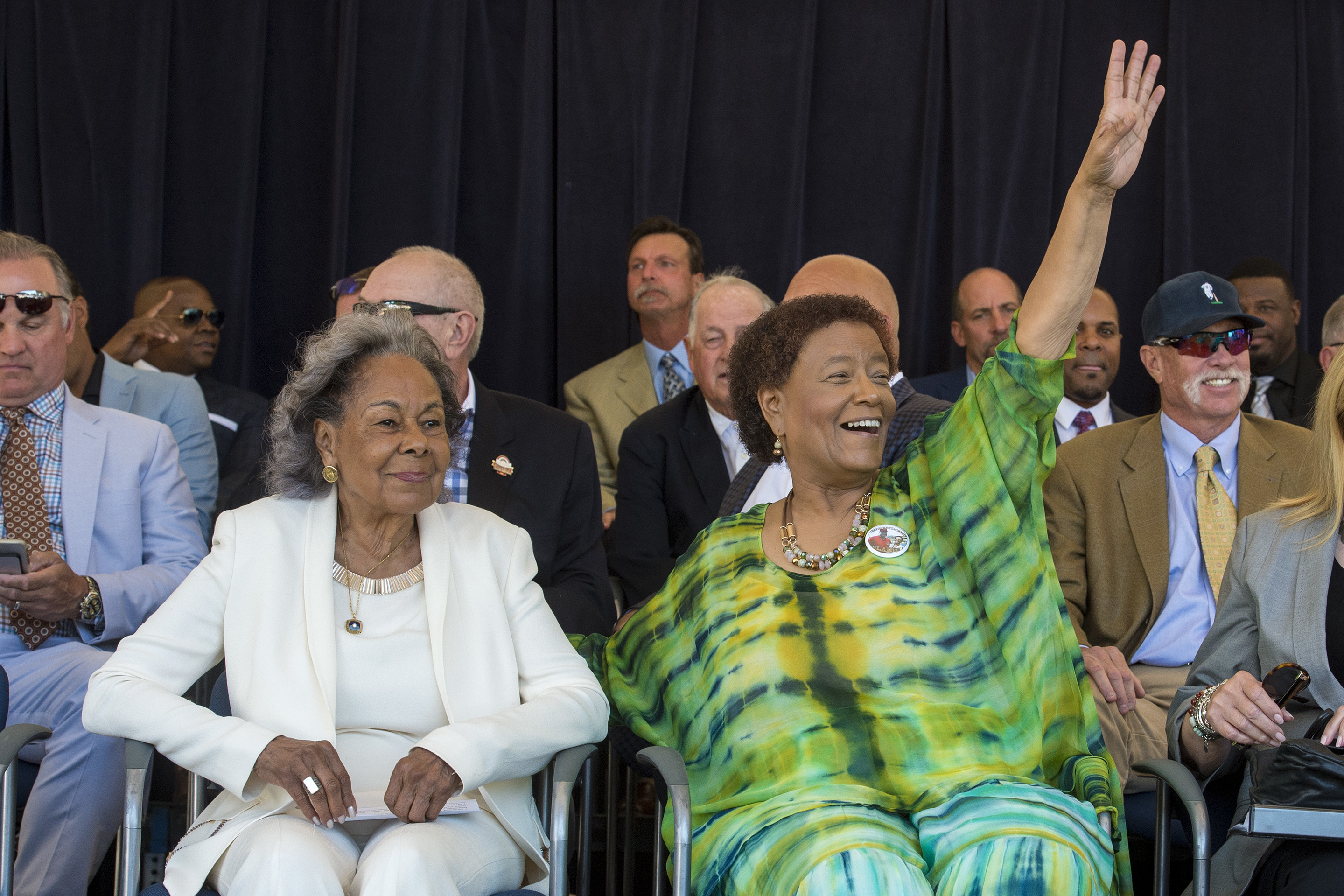"""Claire Smith (right) waves to family and friends gathered to see her accept the J.G. Taylor Spink Award from the Baseball Hall of Fame at Doubleday Field in Cooperstown, NY, July 29, 2017. At left is Rachel Robinson, the widow of famed player Jackie Robinson, who was given the John J. """"Buck"""" O'Neil Lifetime Achievement Award."""