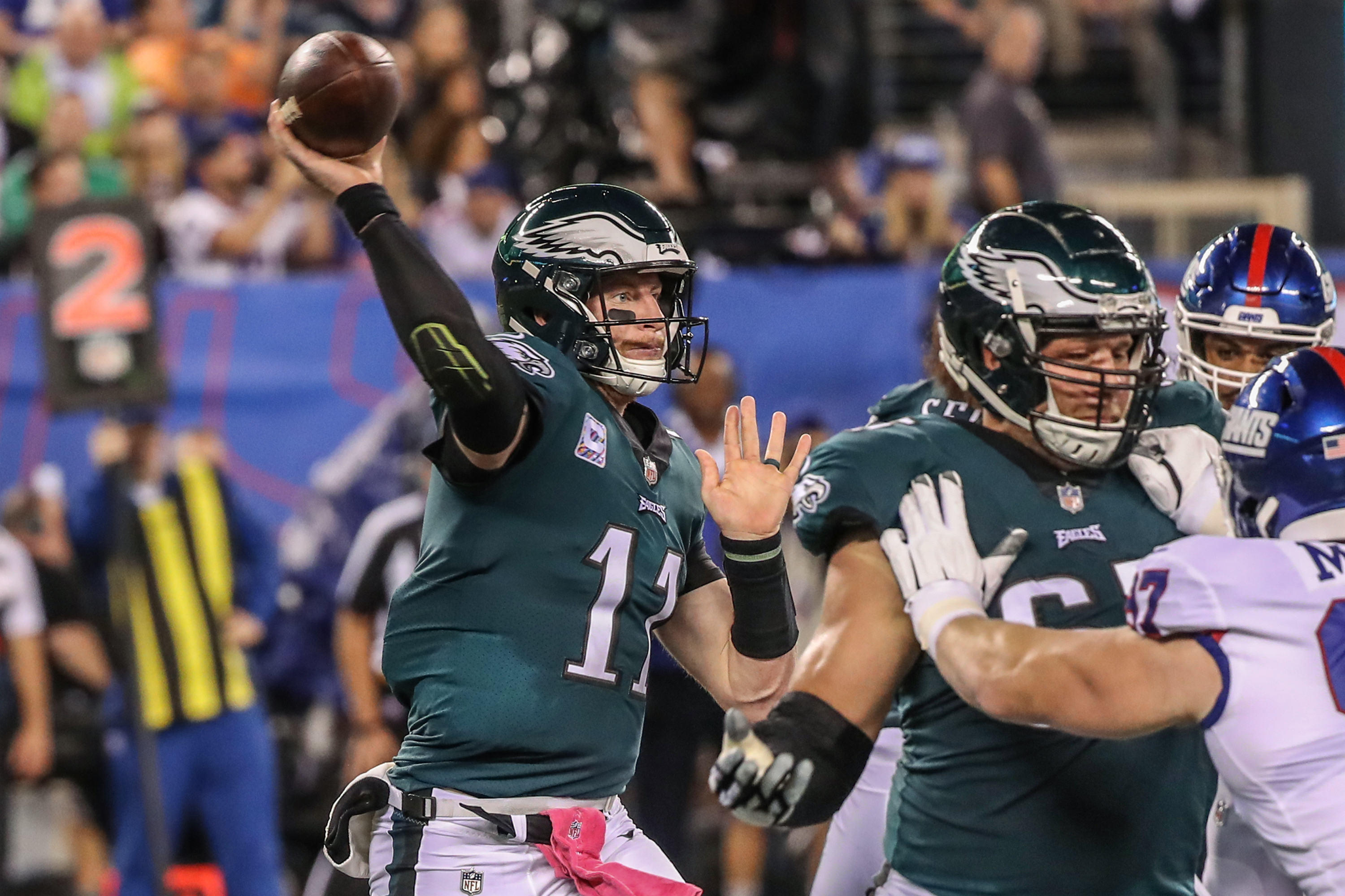 As Eagles quarterback Carson Wentz, left, steps up to pass the ball Eagles tackle Lane Johson, right, keeps a Giant defender at bay so Wentz can have time to throw in Thursdays game against the Giants on October 11, 2018. MICHAEL BRYANT / Staff Photographer