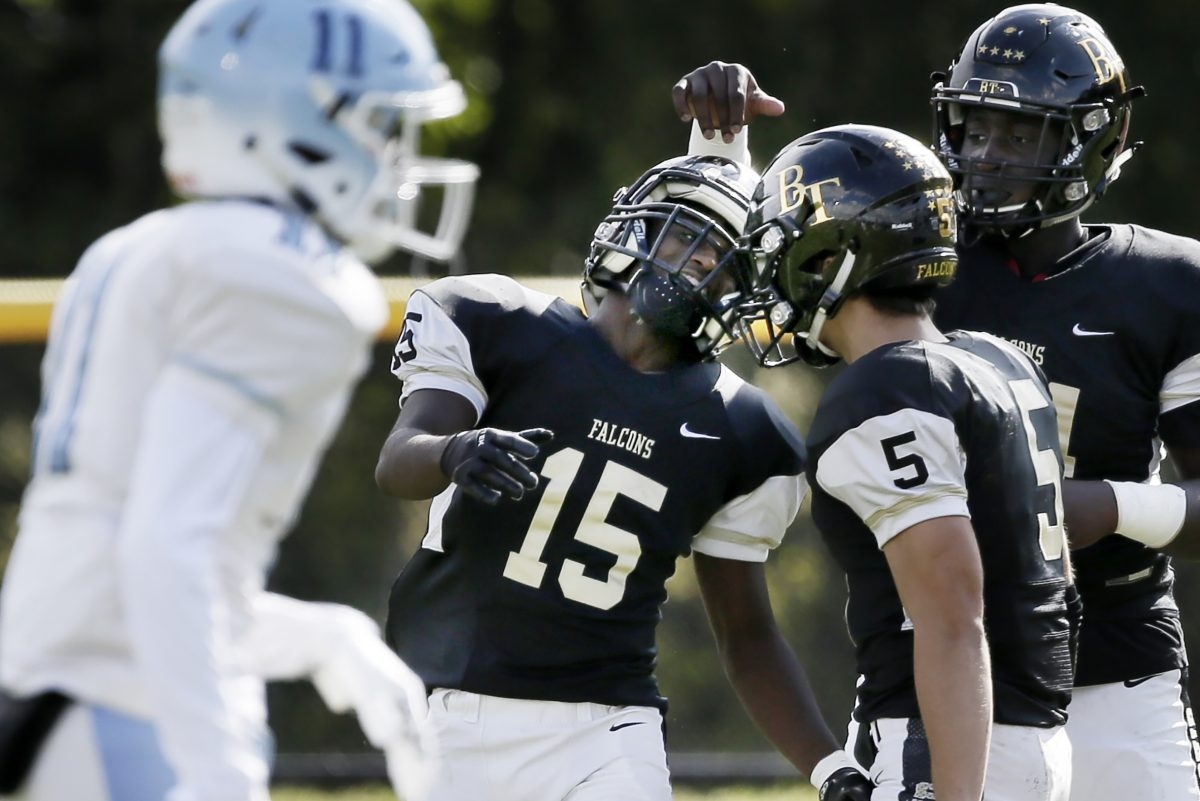 Rodney Vines is surrounded by his teamates after he scored on a long run as Burlington Township beat Highland, 14-13.