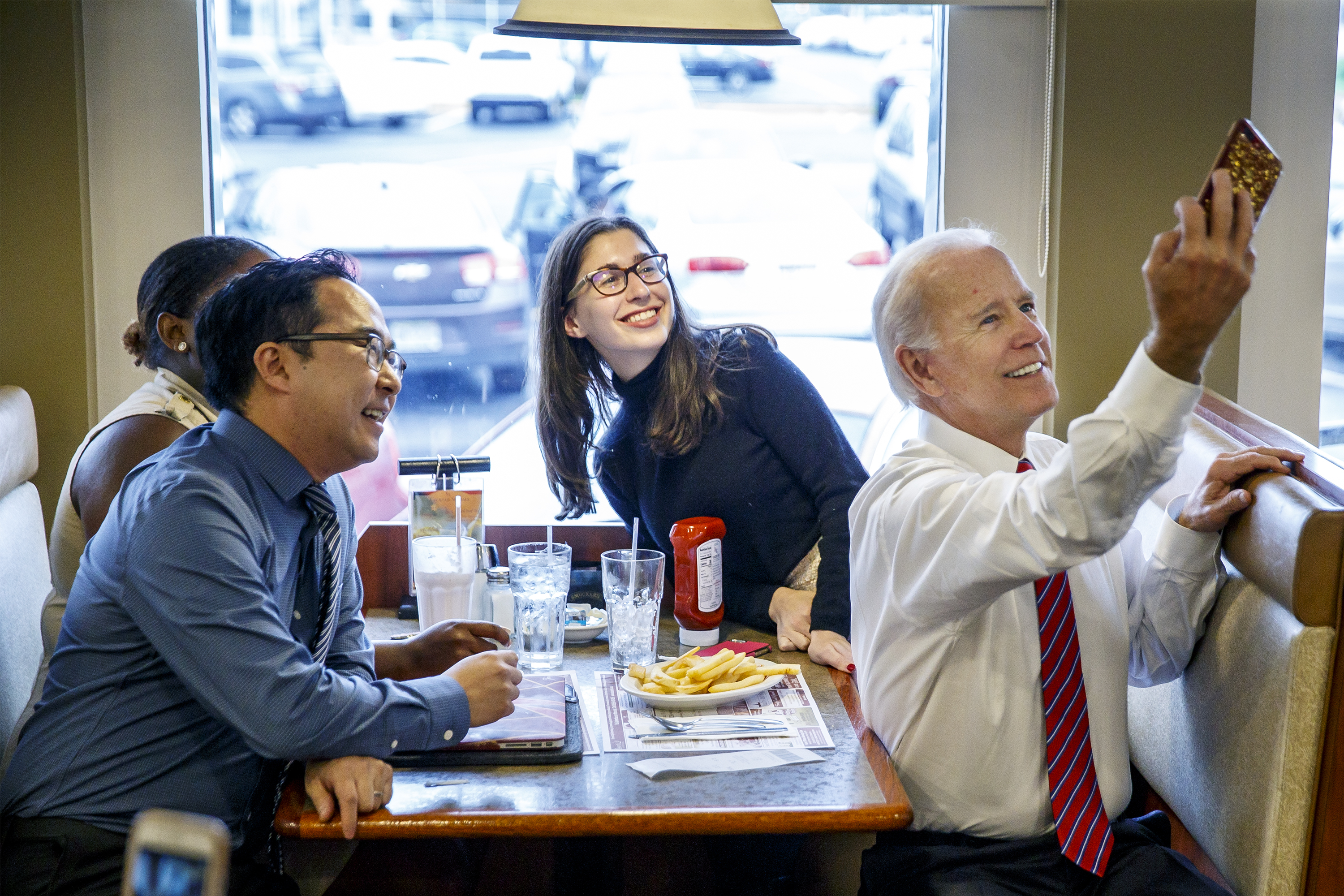Former vice president Joe Biden, right, takes a selfie with Democratic candidate Andy Kim, left, and diners at the Golden Dawn Diner in Willingboro , NJ on October 15, 2018.