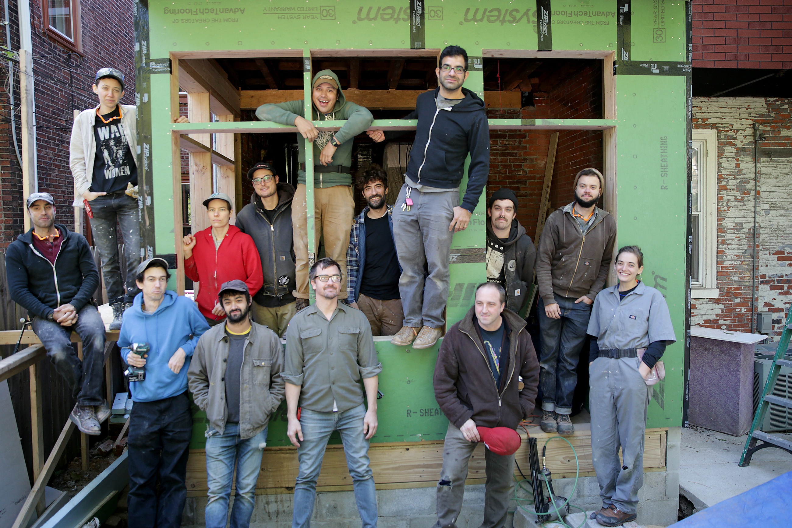 A group of carpenters who will become the coop Hivemind Philly, pose at a property on the 4200 block of Regent Square in Philadelphia, PA on October 24, 2018. Left to right: David Bevacqua, RC Connor, Drew Mitchell, Ashley Arnwine, Zach Ogden, Arthur Zahor, Francisco Grajales, Michael Heinzler, Roman Salcic, Ricky Perez, James Strauss, Spencer Dilday, Sampson Smoot, and Jamie Blair.