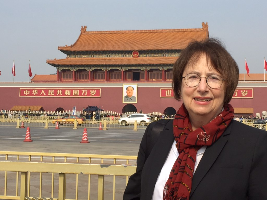 Trudy Rubin at Tiananmen Square with Forbidden City in the background. A portrait of Mao Zedong hangs prominently.