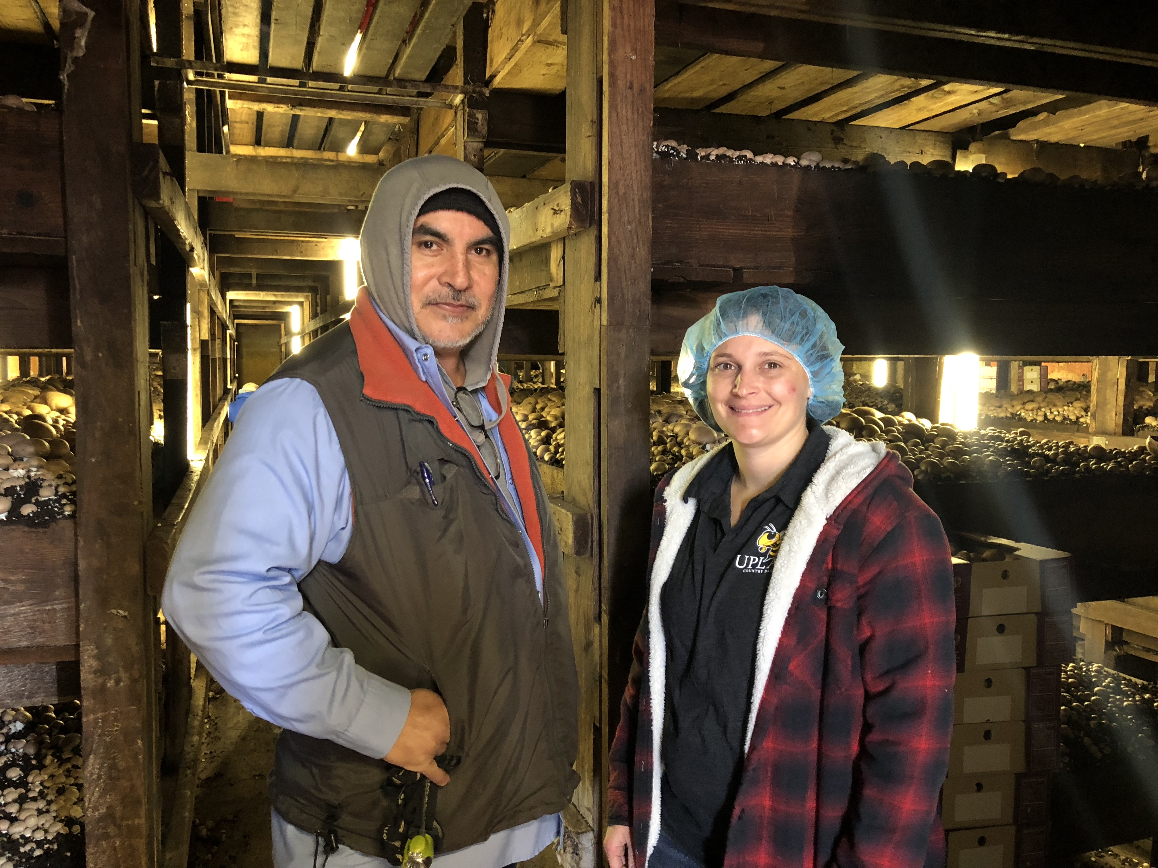 Alfredo Bedolla, a Mexican immigrant who has worked at Mother Earth Organic Mushrooms 16 years, and Meghan Klotzbach, a sixth generation farmer at Mother Earth, pose in front of the long crates of mushrooms waiting to be picked.