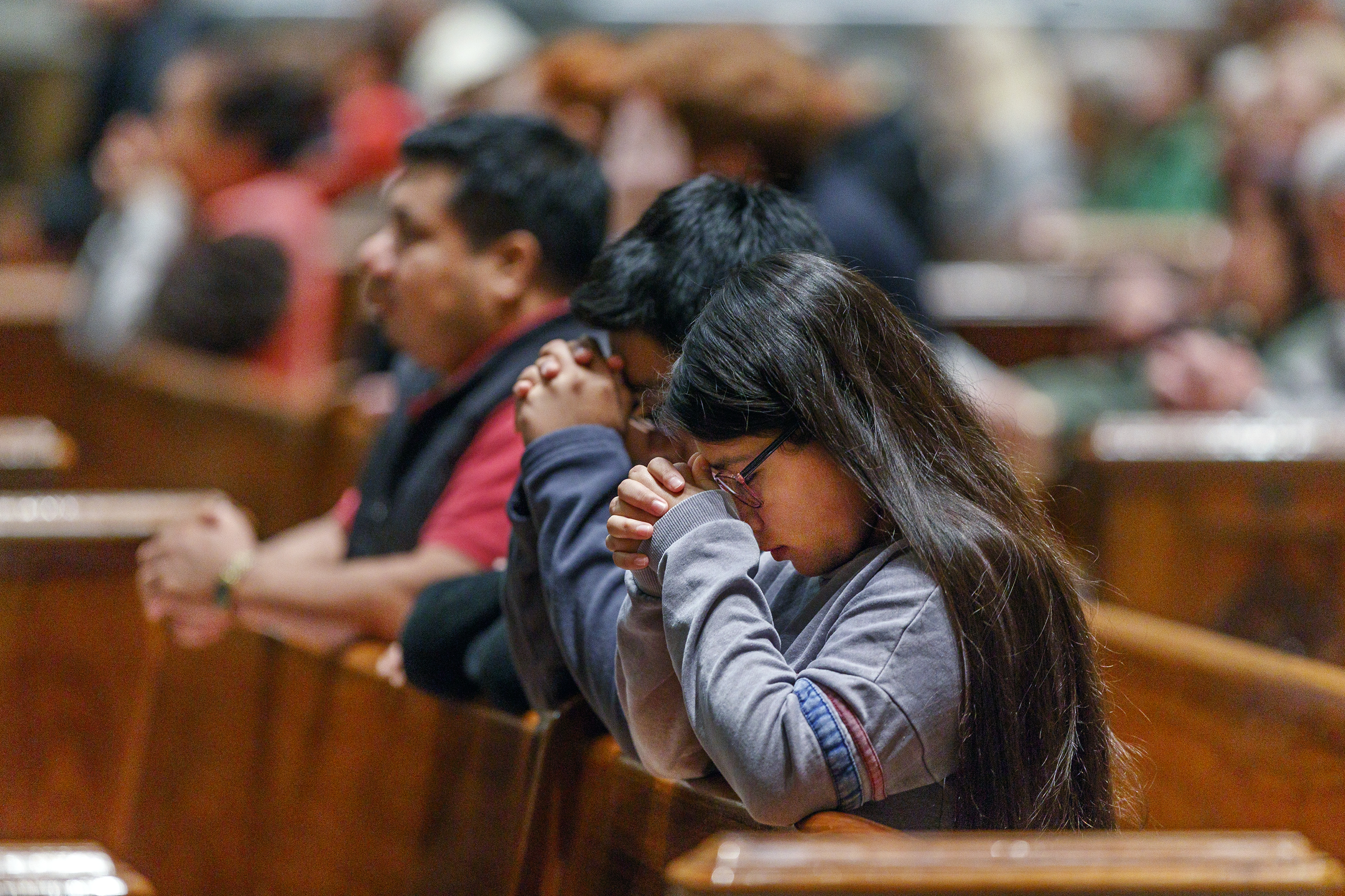 A family prays at the 9:30 morning mass at the Basilica of St Peter and Paul on October 28, 2018, as Monsignor Louis A. D'Addezio offers up prayers for the families of those killed and injured at the synagogue shooting in Pittsburgh on Saturday.