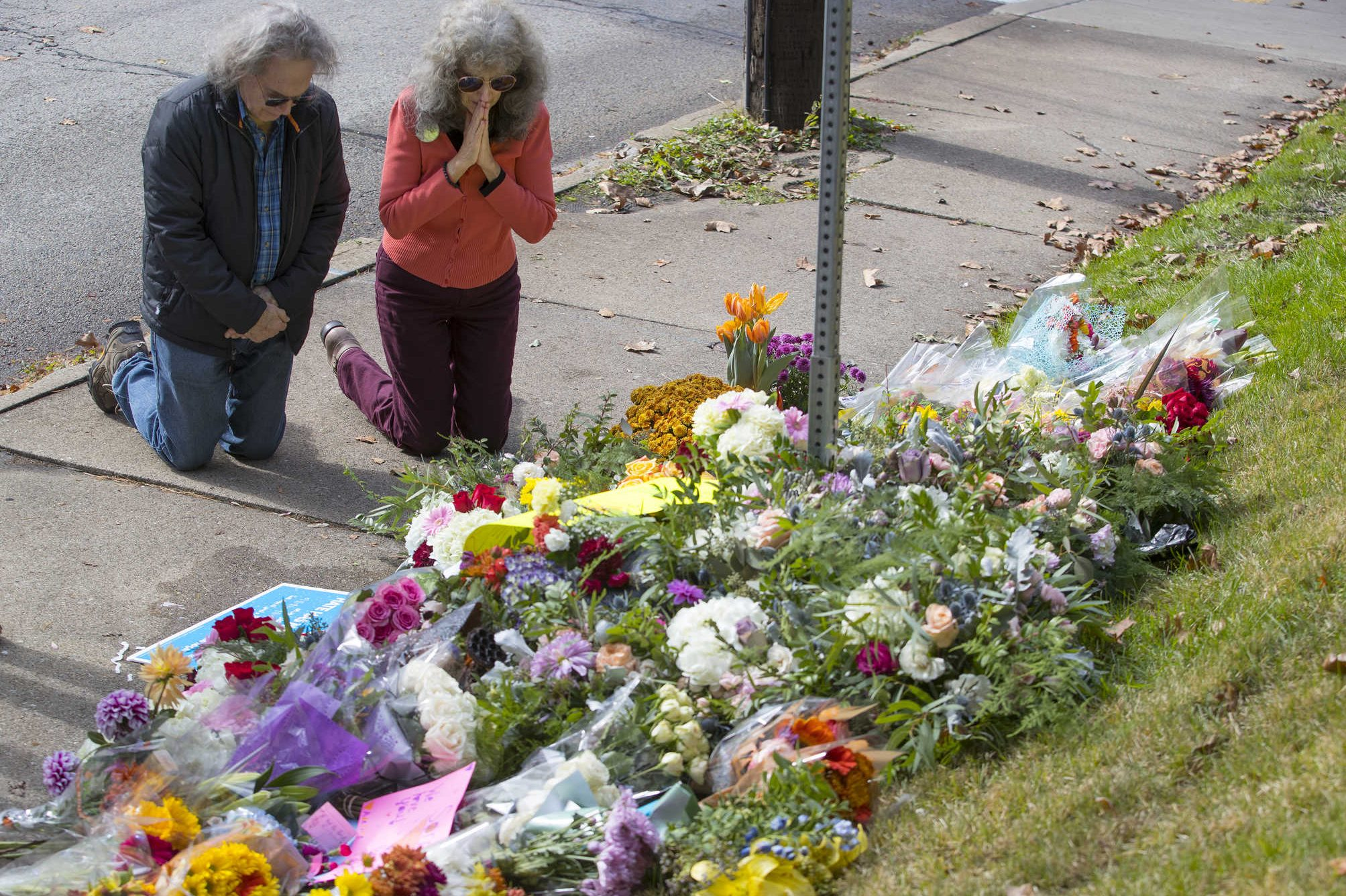 A couple kneels before a memorial at Murray and Wilkins Ave. on Oct. 28, 2018. The memorial was for the 11 people that were killed at the shooting at the Tree of Life Synagogue.