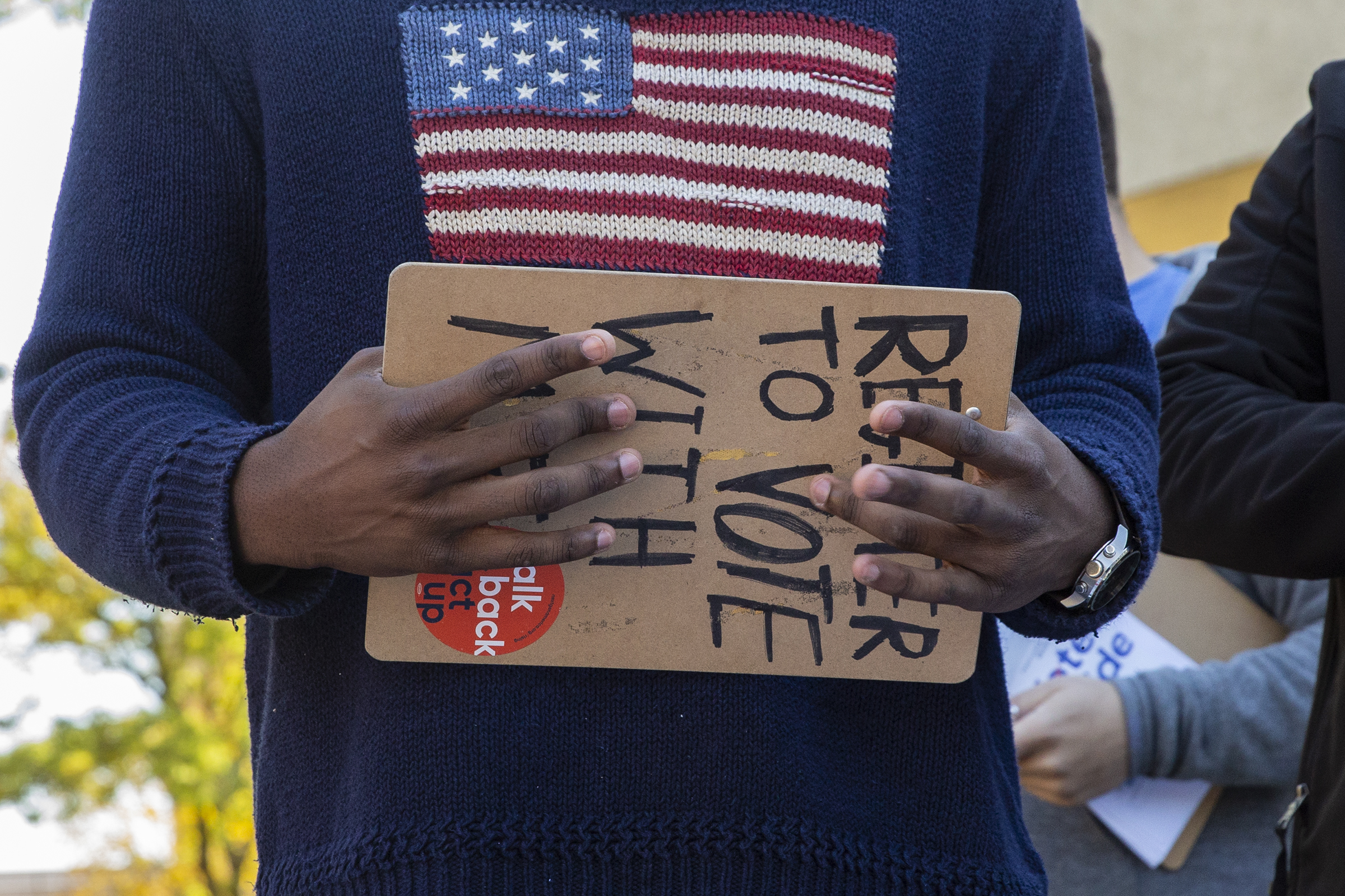 Khalil Bryant holds a clipboard as he encourages students to pledge to vote on Election Day.
