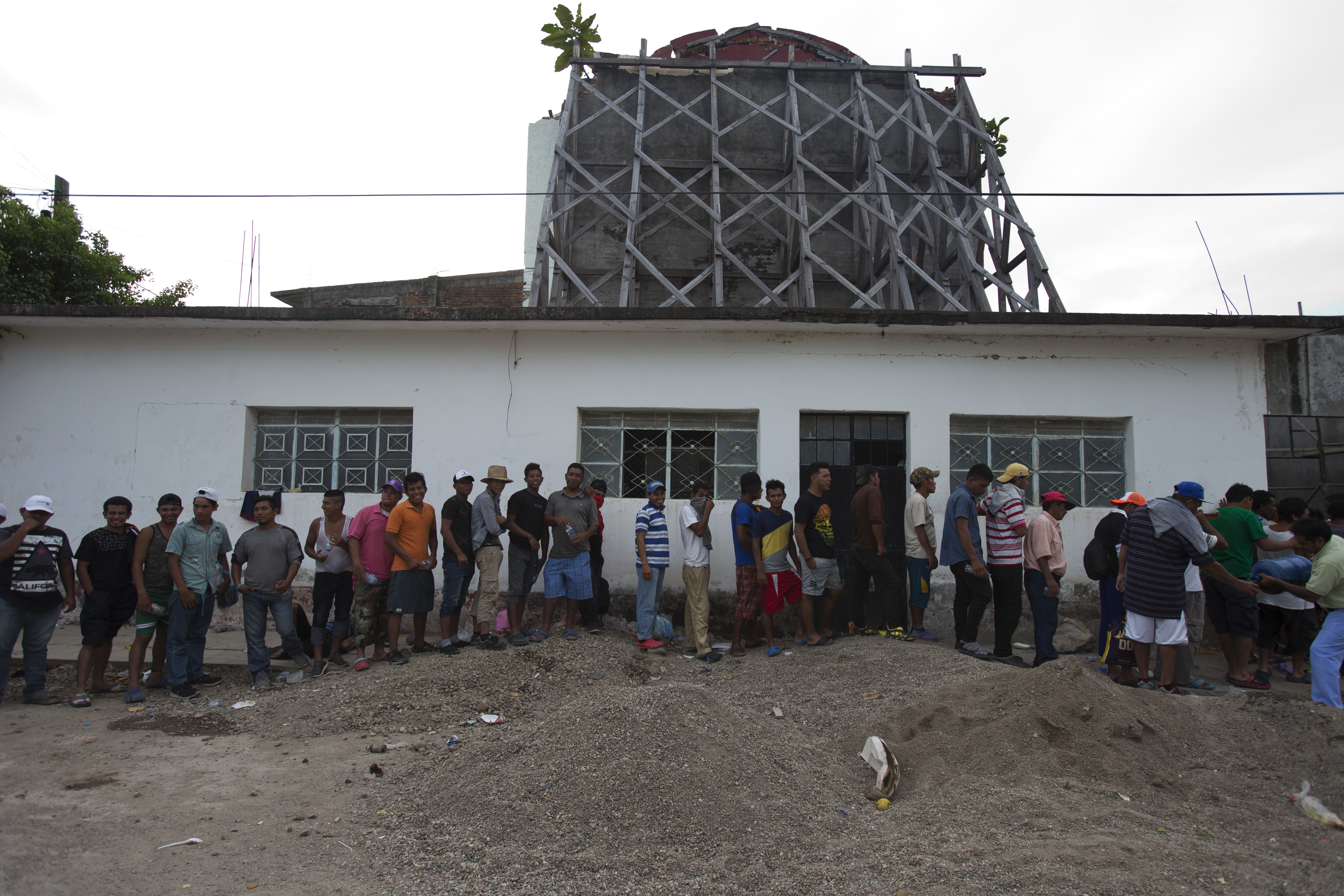 Migrants line up to receive food at a church that was heavily damaged in a 2017 earthquake, as a thousands-strong caravan of Central Americans hoping to reach the U.S. border stops for the night in Niltepec, Oaxaca state, Mexico on Monday.