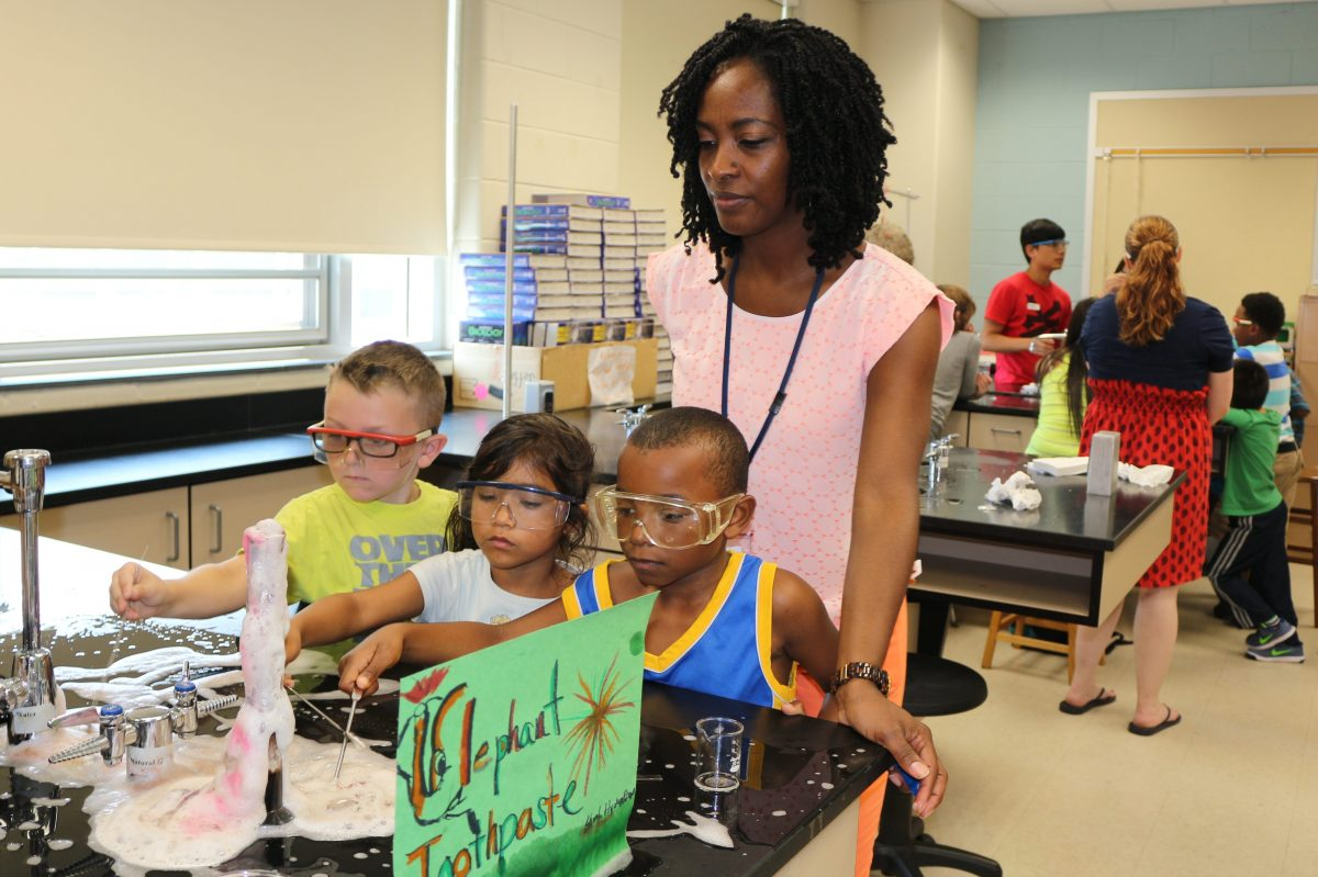 Pennsauken elementary students (l-r) Logan Mayberry, 6, Maryel Torres, 5 and Javon McNatt, watch a toothpaste science experiment as Principal Tanya Harmon watches. They are participating in free summer enrichment classes offered by the district.