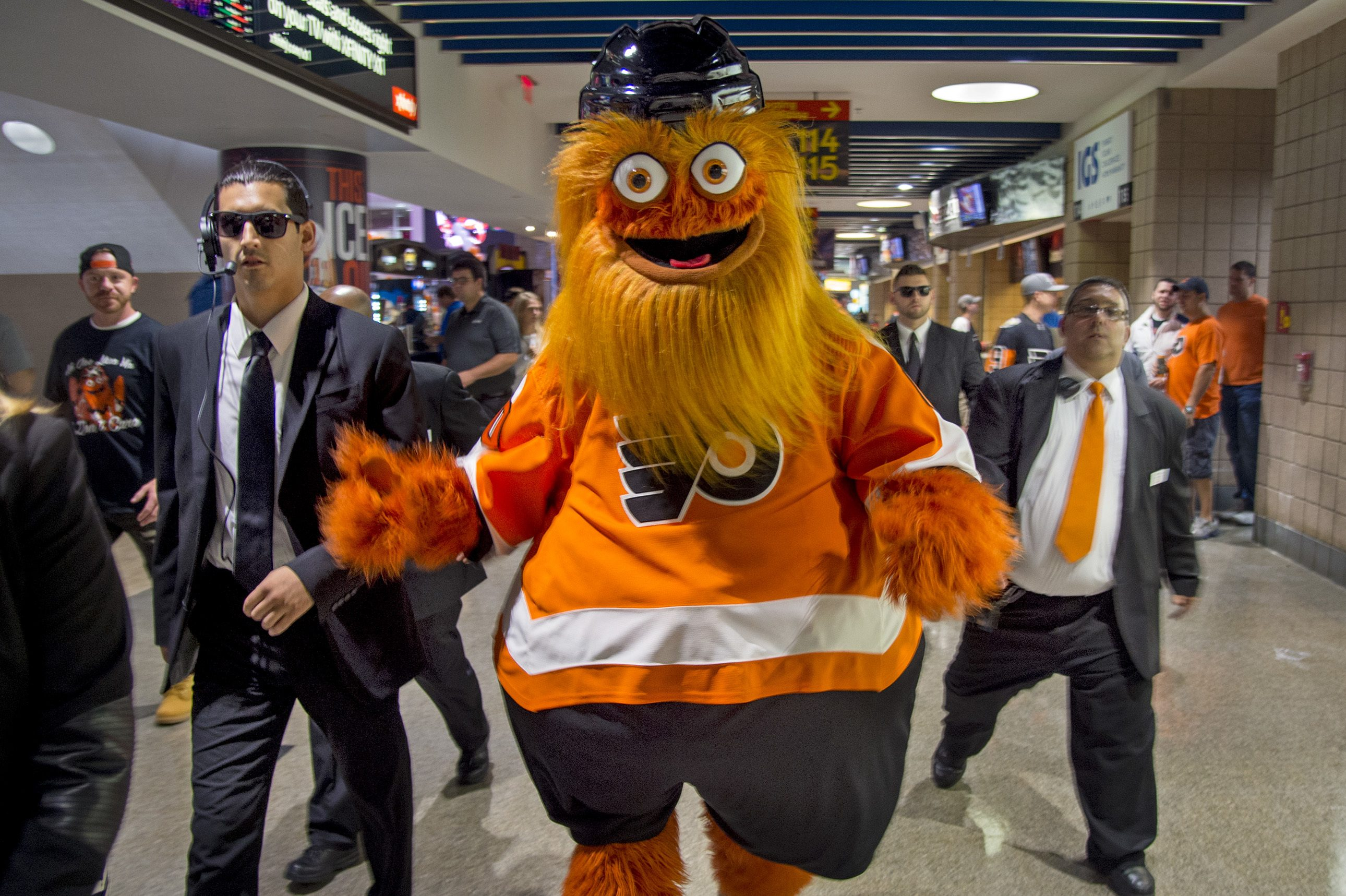 "Gritty, the Philadelphia Flyers´ new mascot, walking on a Wells Fargo Center concourse with his ""security detail."""