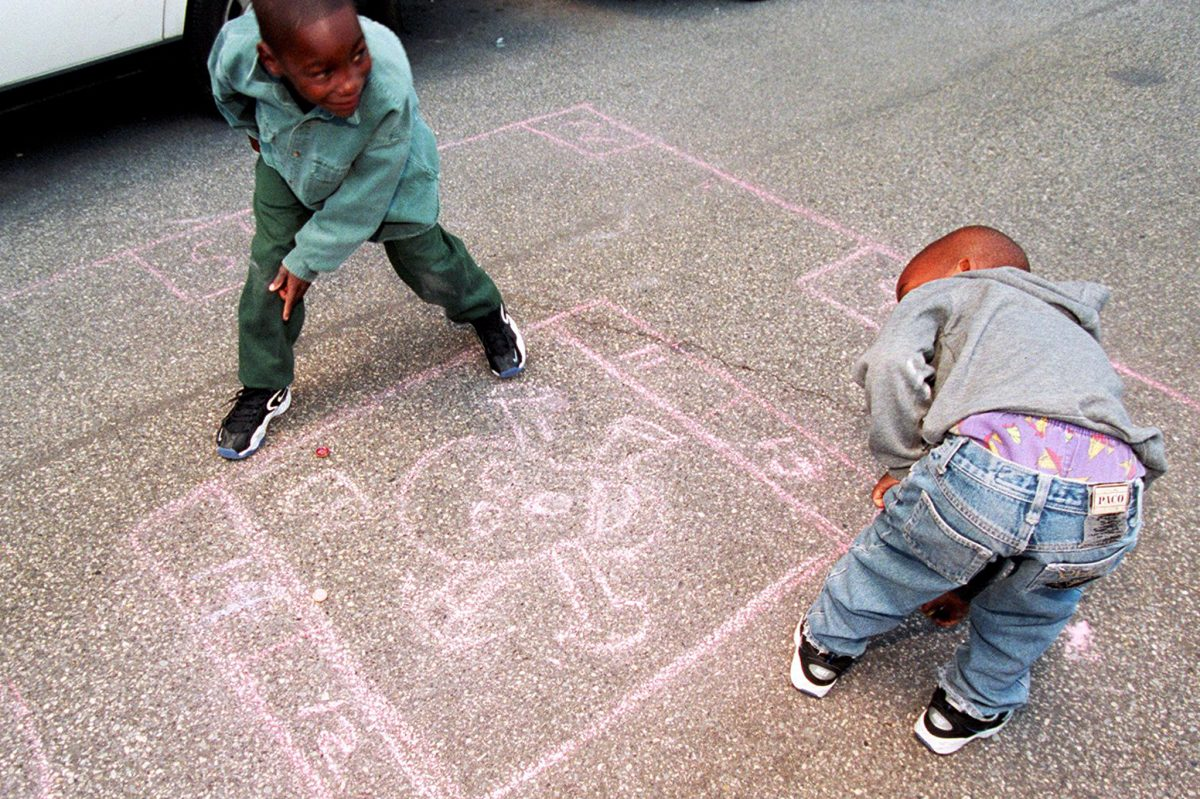 During the Rowhouse Olympics in Old City in 1997, brothers Khalil Cheely, 7, (left) and Joshua, 6, of West Philadelphia play a game of deadbox.