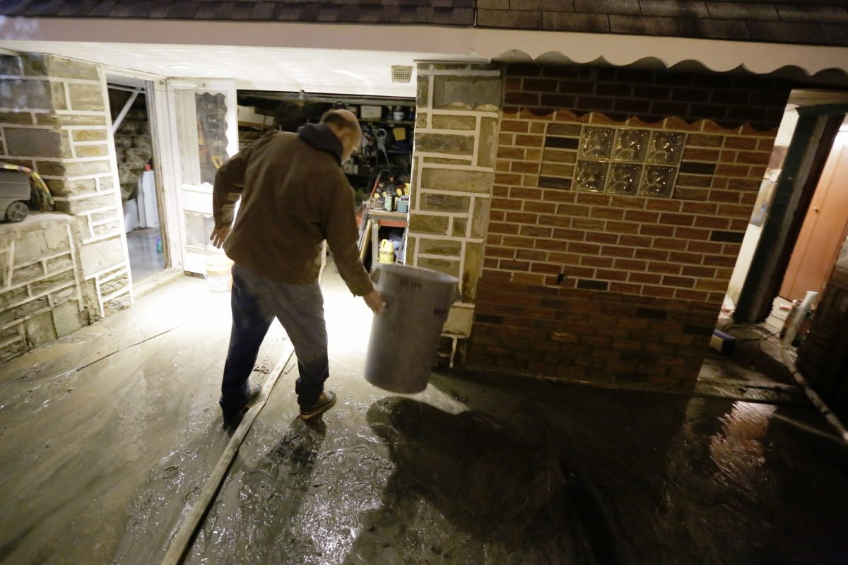 Ed Volmer moves a trash can as water still runs into his basement and garage hours after a large water main burst flooding part of his home on Millbrook Rd. in Phila., PA on January 5, 2017 ELIZABETH ROBERTSON / Staff Photographer 