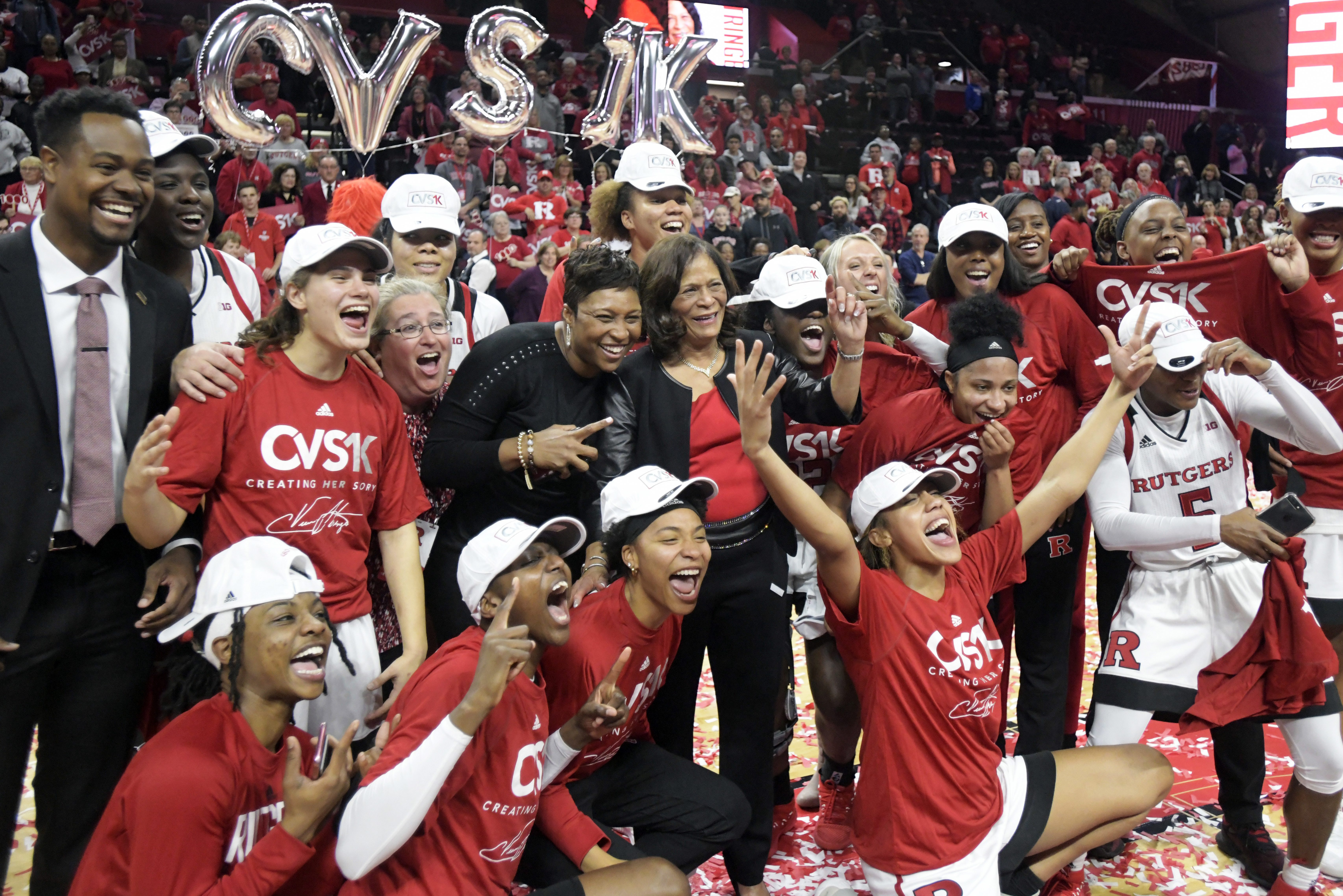 Rutgers coach C. Vivian Stringer, center, poses with her team after they defeated Central Connecticut for her 1,000th career win.