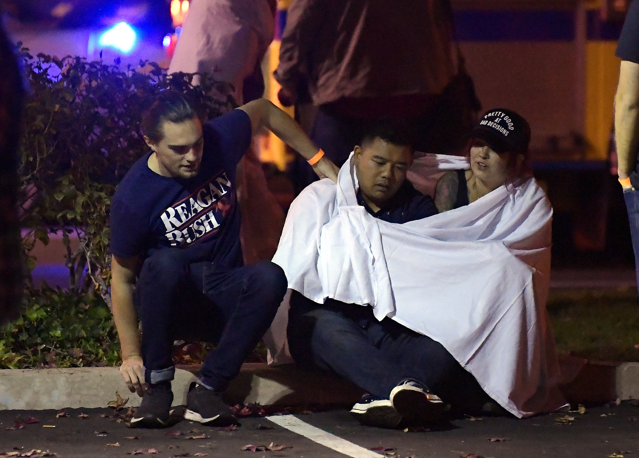 """People comfort each other as they sit near the scene Thursday, Nov. 8, 2018, in Thousand Oaks, Calif. where a gunman opened fire Wednesday inside a country dance bar crowded with hundreds of people on """"college night,"""" wounding 11 people including a deputy who rushed to the scene. Ventura County sheriff´s spokesman says gunman is dead inside the bar"""