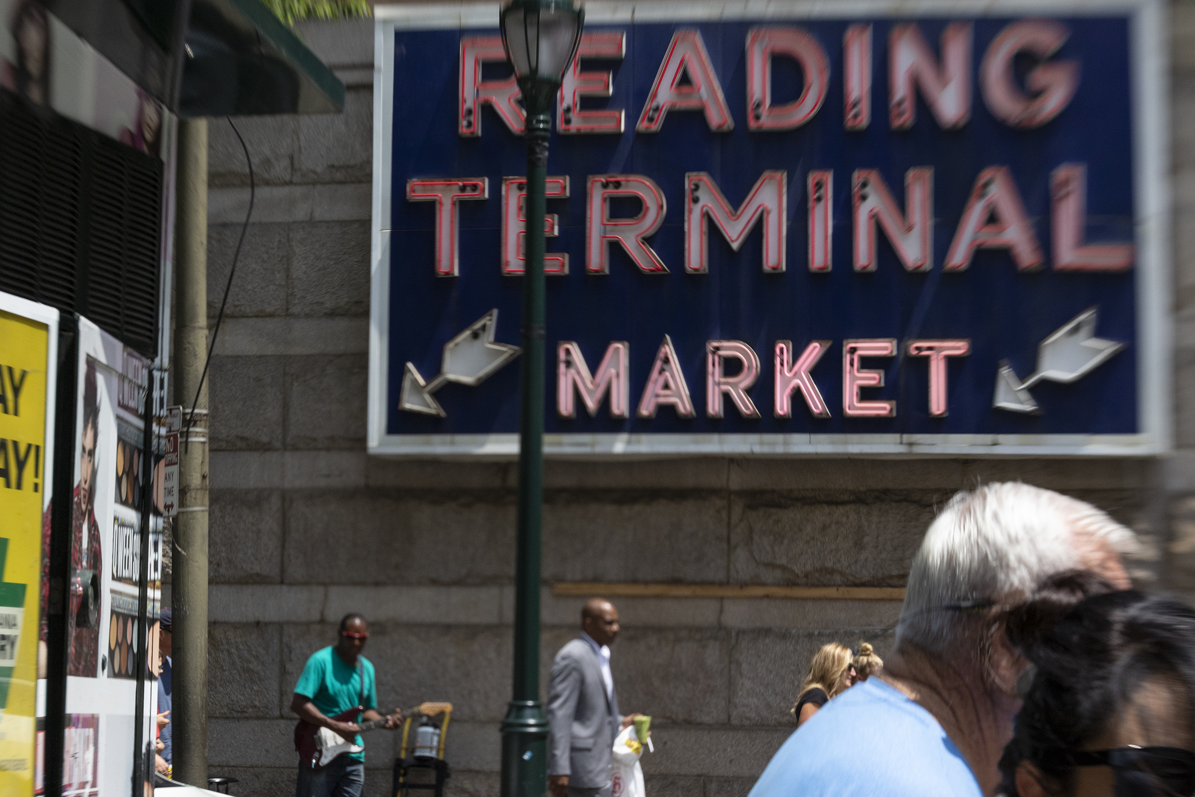People walk by a sign pointing towards Reading Terminal Market at 51 N. 12th St. on July 27, 2018.