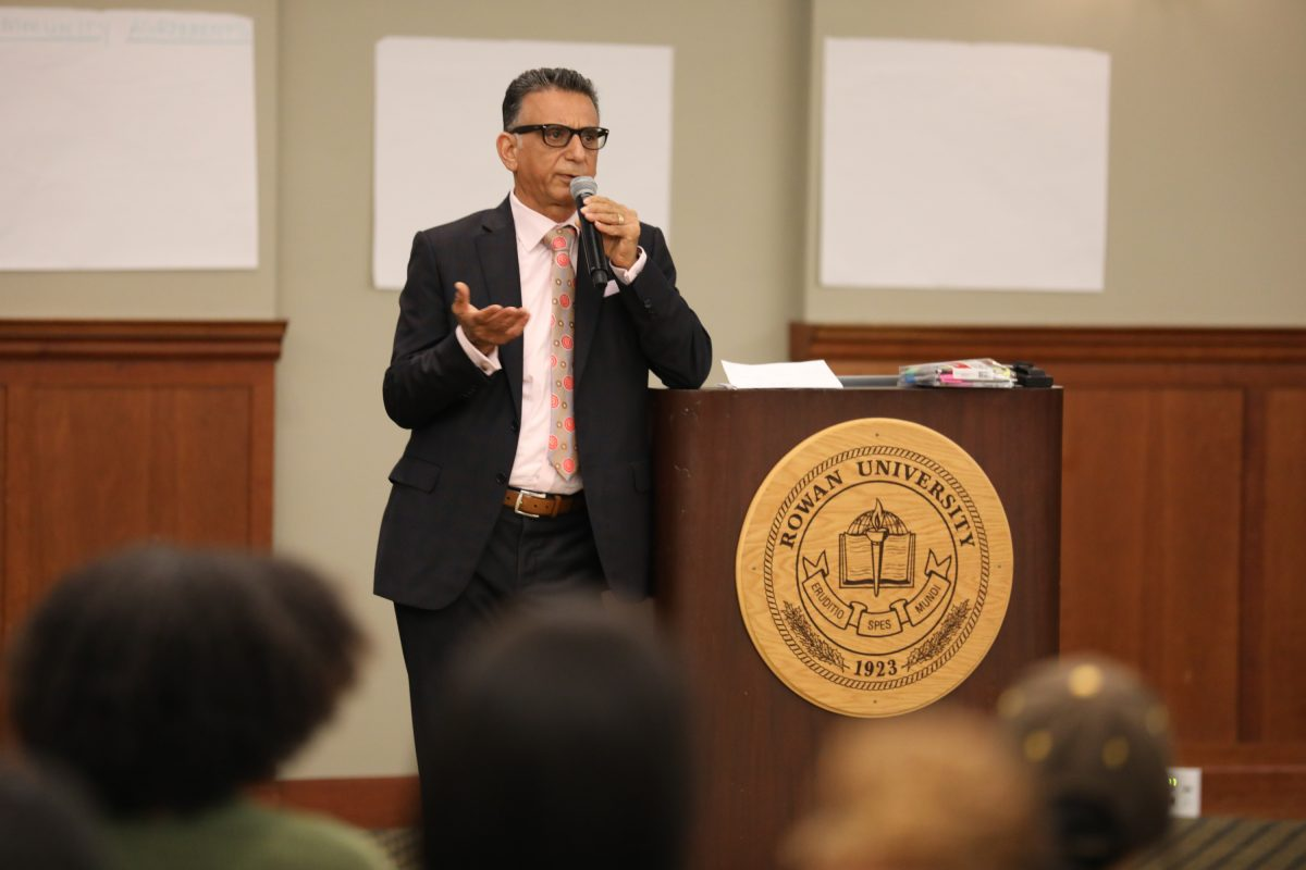 Rowan President Ali Houshmand speaks at a town hall meeting in October. On Friday, he reversed an earlier policy requiring student athletes wear shirts while practicing.