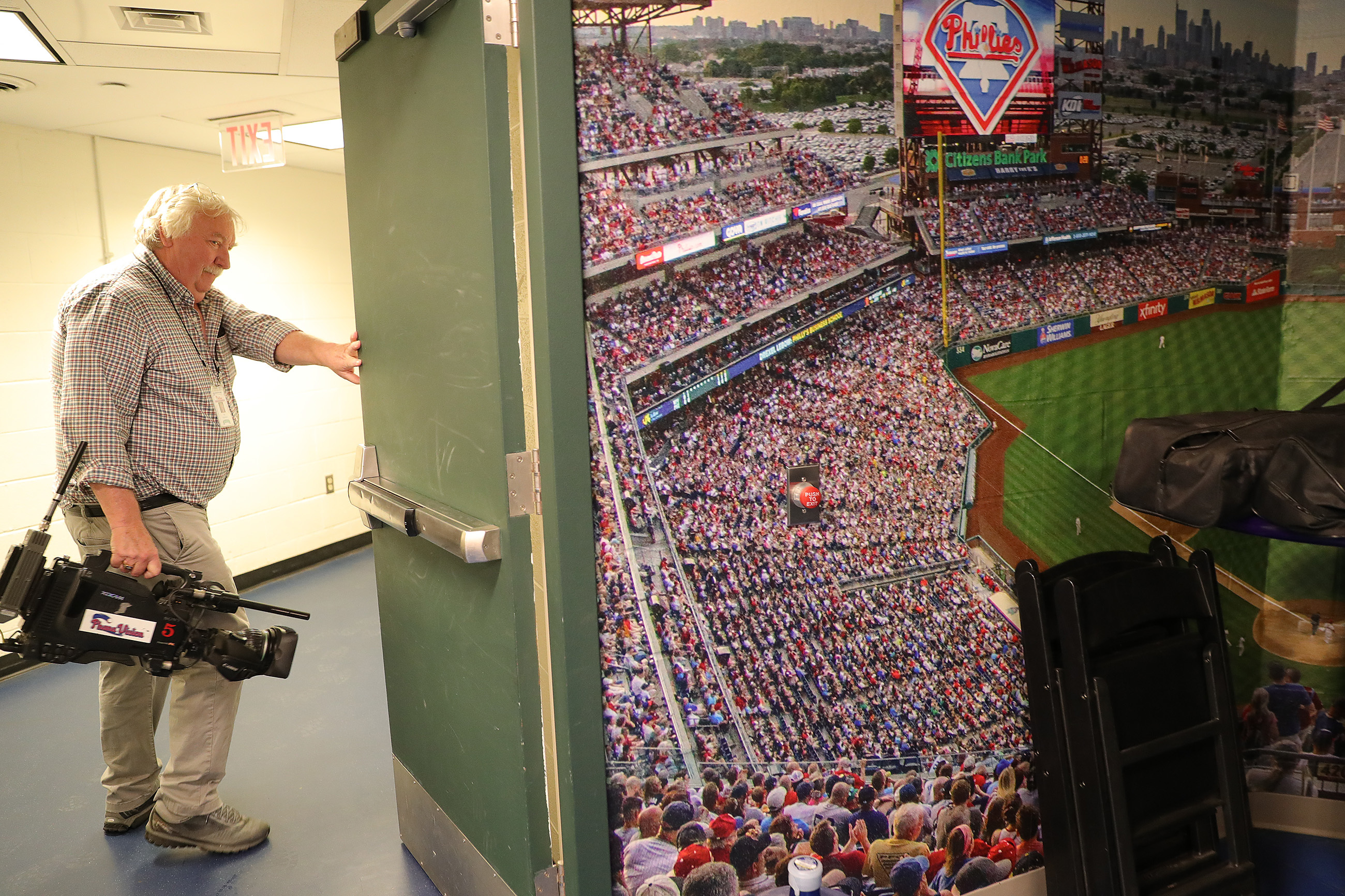 Phillies video man, Dan Stephenson, walks through a hallway near the clubhouse at Citizens Bank Park.