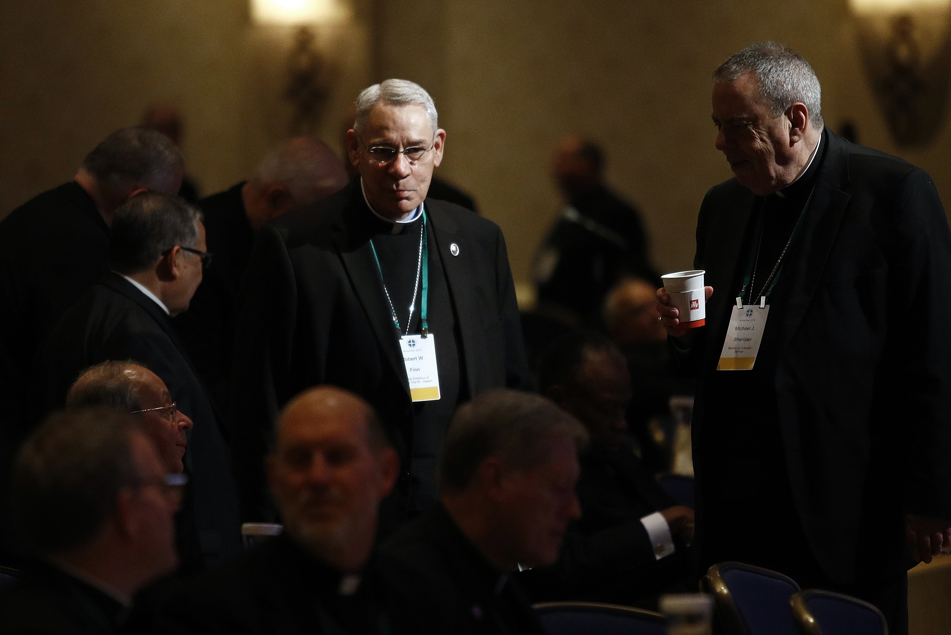 Bishop Emeritus Robert Finn, of Kansas City, Mo., center, speaks with fellow members of the United States Conference of Catholic Bishops at the annual fall meeting Tuesday in Baltimore.