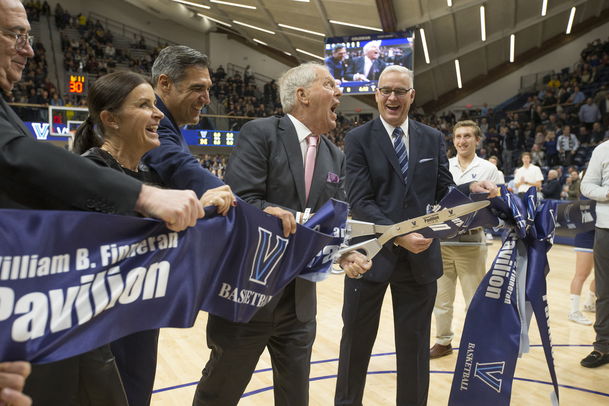 William Finneran, center, cuts the ribbon to officially open the Finneran Pavilion before the game against Villanova and Michigan on Nov. 14, 2018.