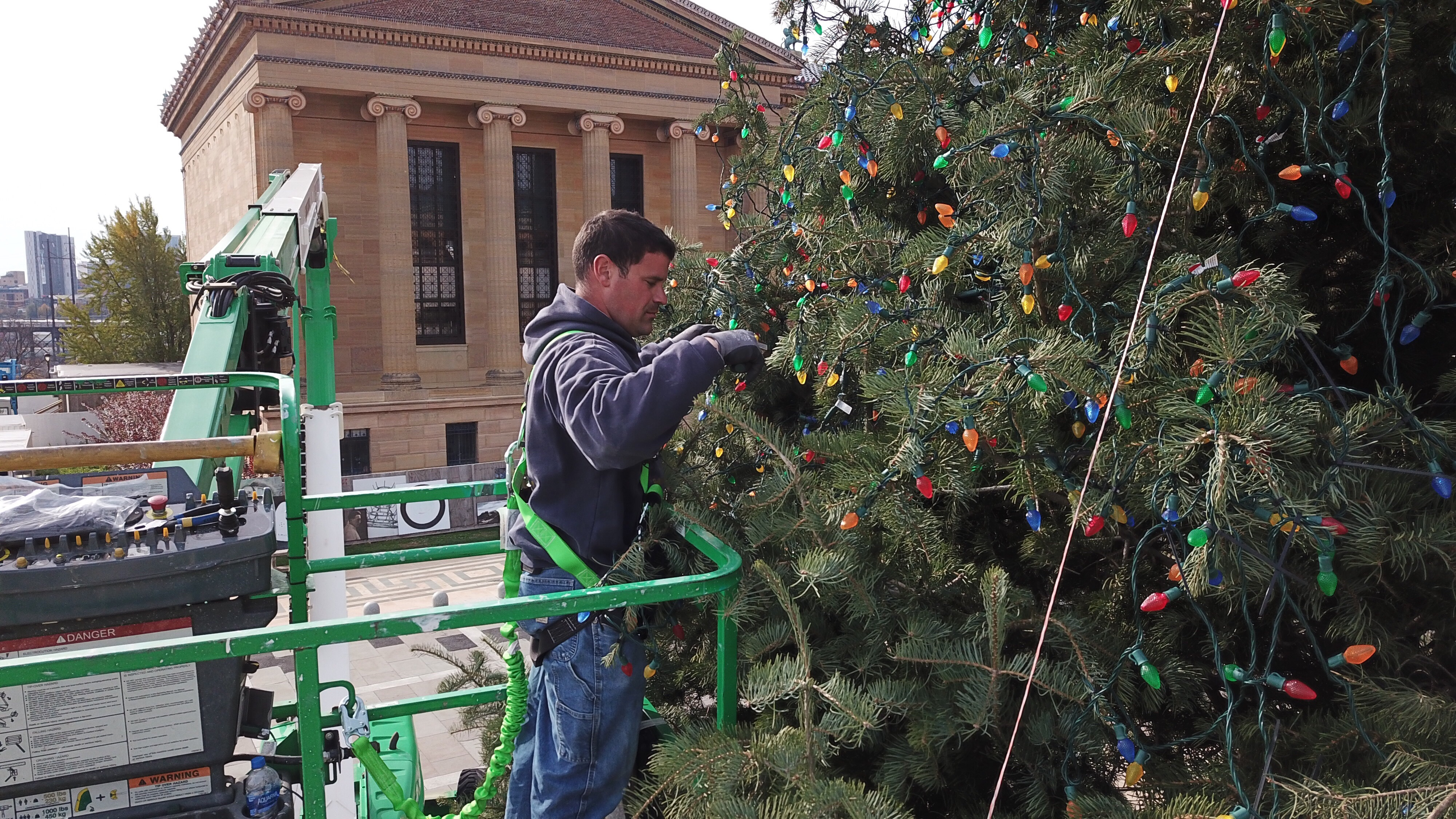 Michael Visco of Local 98 and two other workers attach Colored lights to a Christmas tree atop the Art Museum steps Monday November 12, 2018.