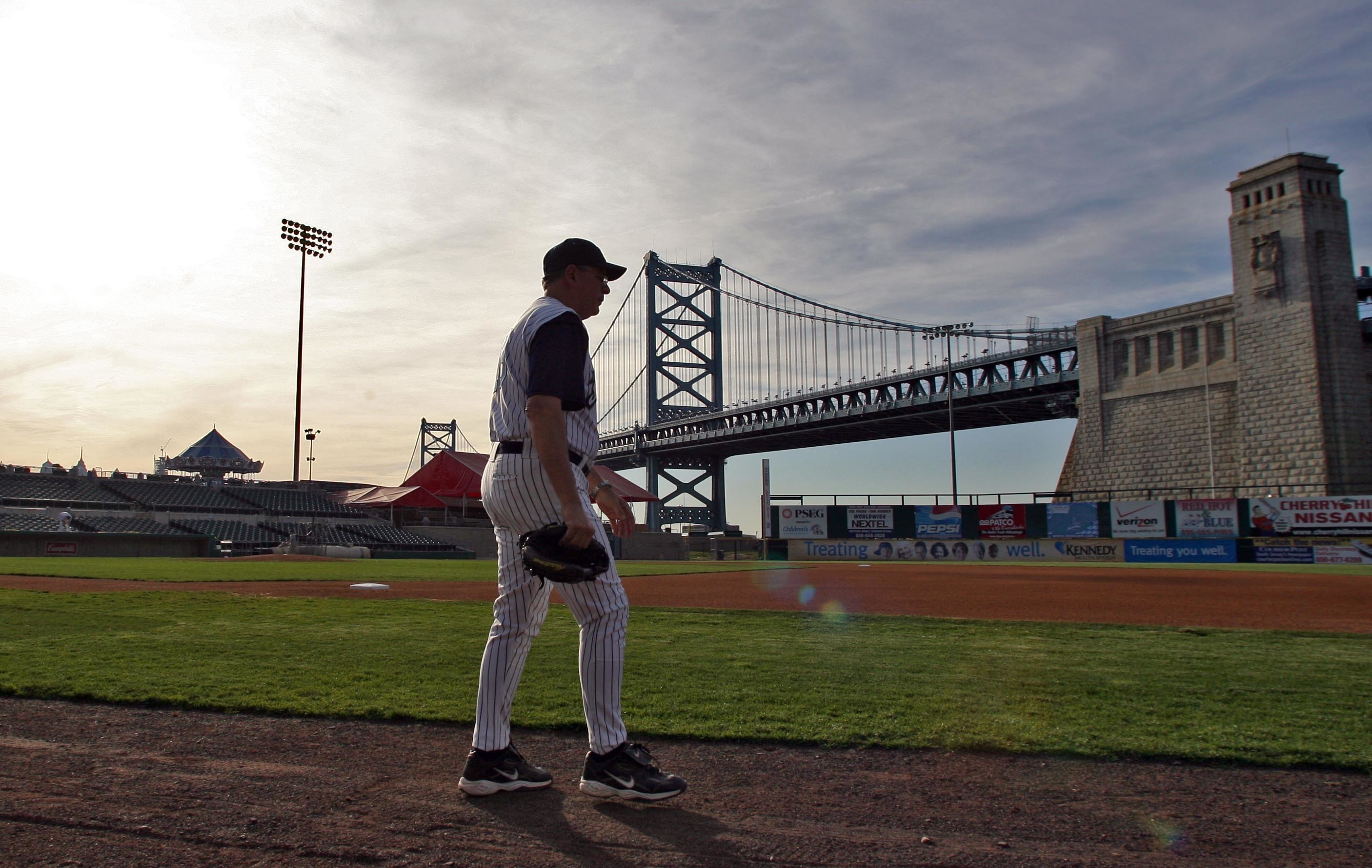 Camden Riversharks Field Manager, Joe Ferguson, walks on Campbell´s Field with the Benjamin Franklin Bridge in the background. File Photograph