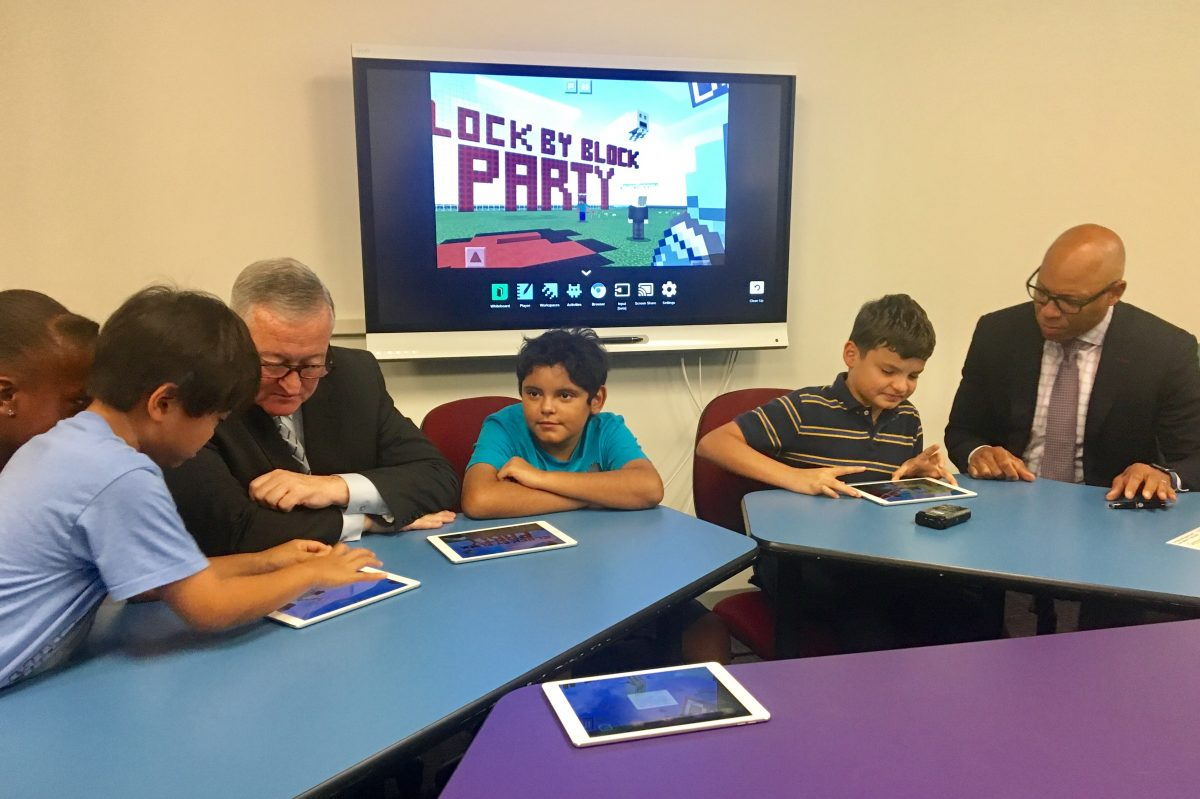 Mayor Kenney (left) and Superintendent William R. Hite Jr. learn how to play Minecraft from a group of Philadelphia children.