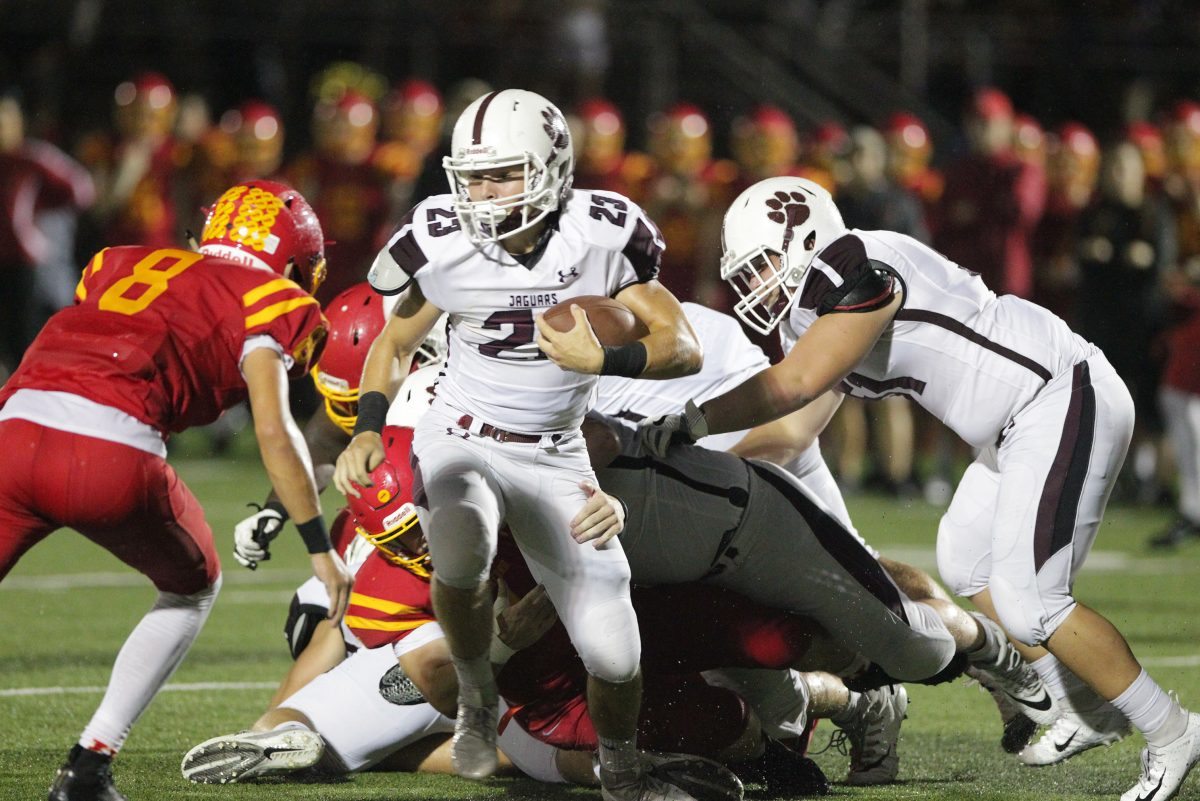 Garnet Valley's Colin Robinson, center, Valley runs for a gain against Central League rival Haverford High.