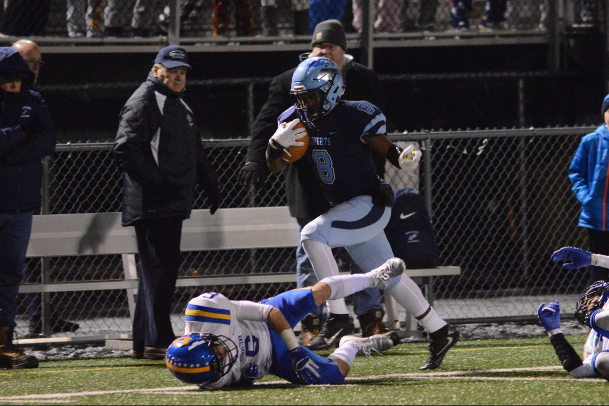 North Penn's Shamar Edwards (8) leaps over Downingtown West's Alex Rosano (6) iun Friday night's PIAA District One Class 6A semifinal contest.