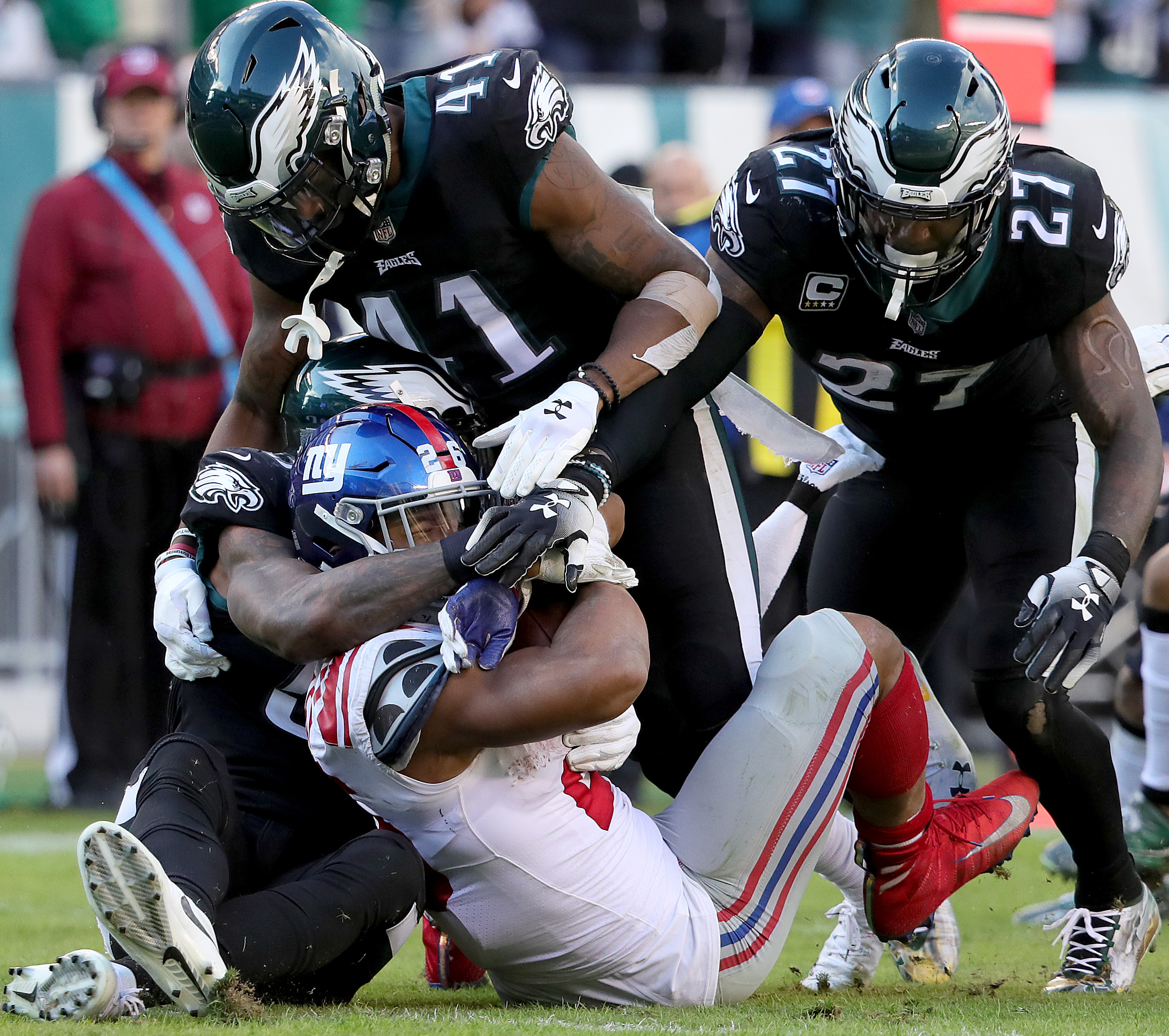 Nigel Bradham (left), De´Vante Bausby (center) and Malcolm Jenkins (right) stop Saquon Barkley in the backfield.