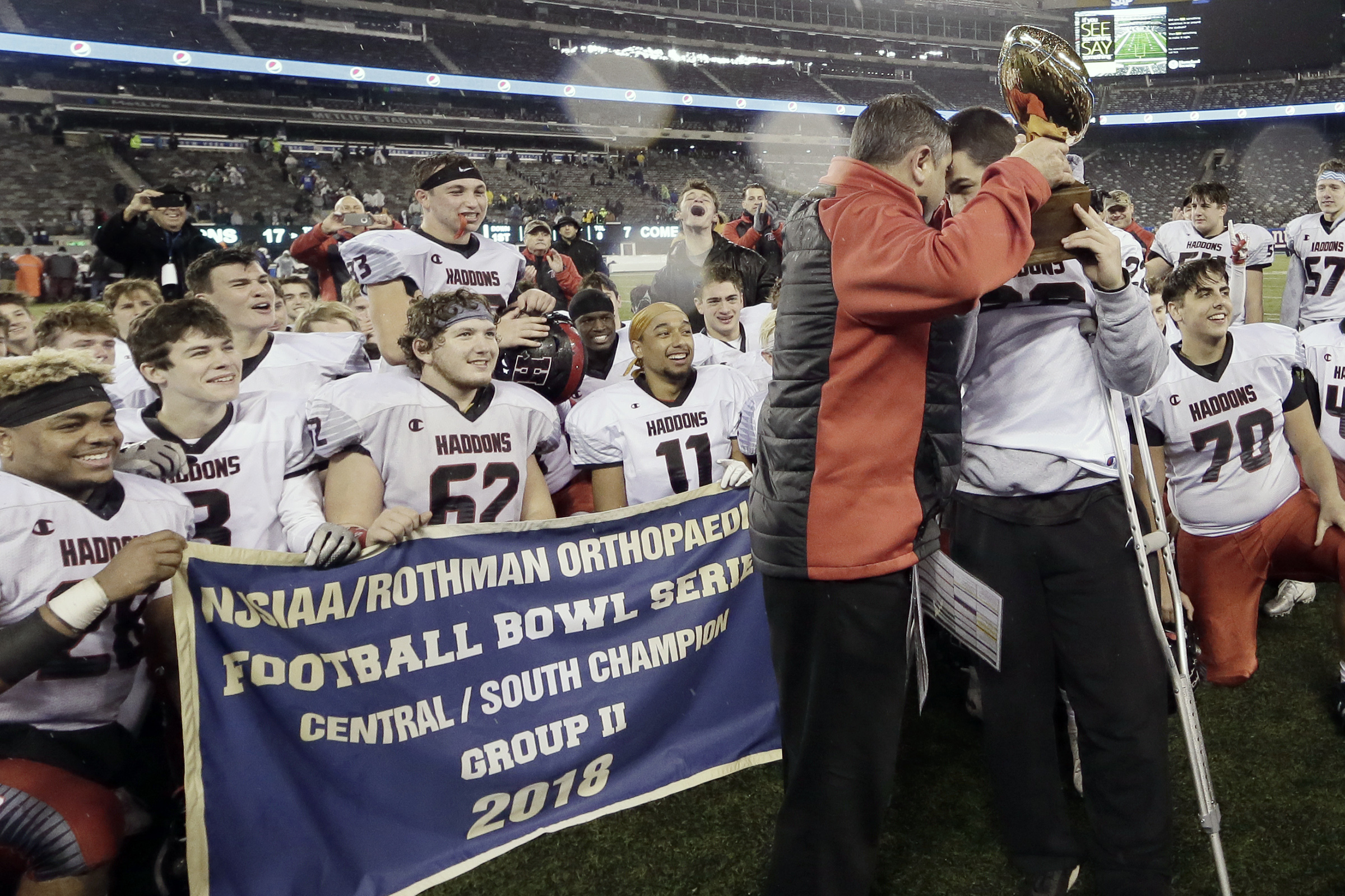 Haddonfield head coach Frank DeLano gives the trophy to injured senior Chris Brown after Group 2 South/Central Bowl Game.