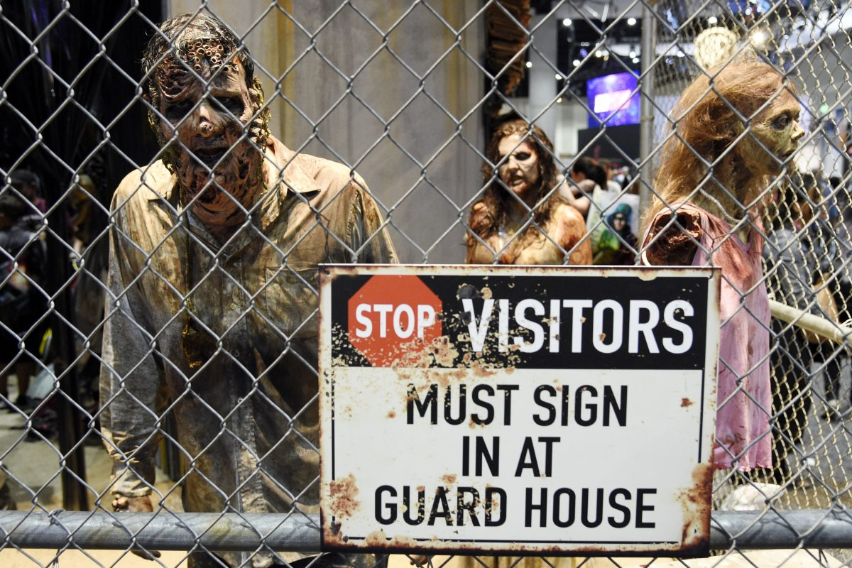 """Zombie characters walk inside a cage at the """"Walking Dead"""" exhibit  during preview night of the 2017 Comic-Con International on July 19, in San Diego."""