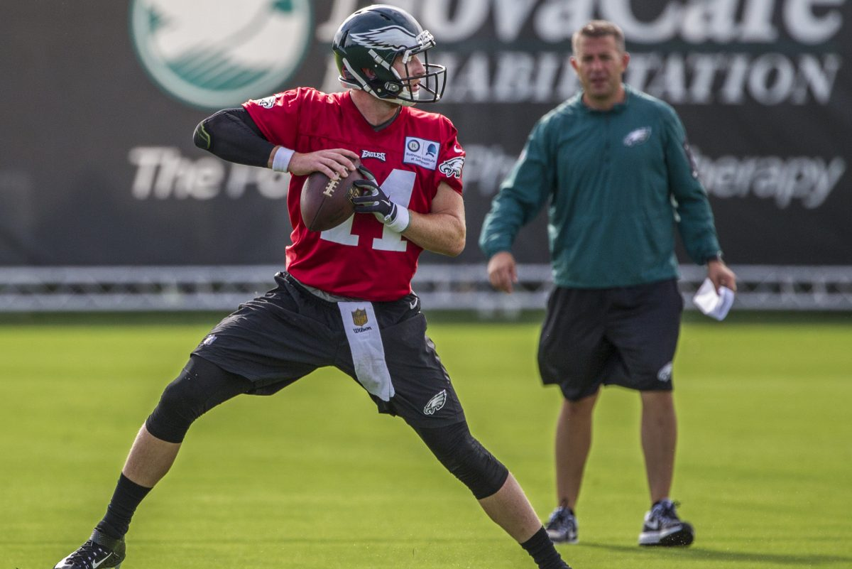 Eagles quarterback Carson Wentz  works through drill under the watchful eye of quarterbacks coach, John DeFilippo on Monday.