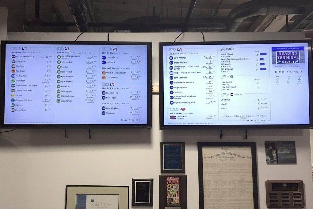 Two screens at Reading Terminal Market display information on transit alternatives for customers.
