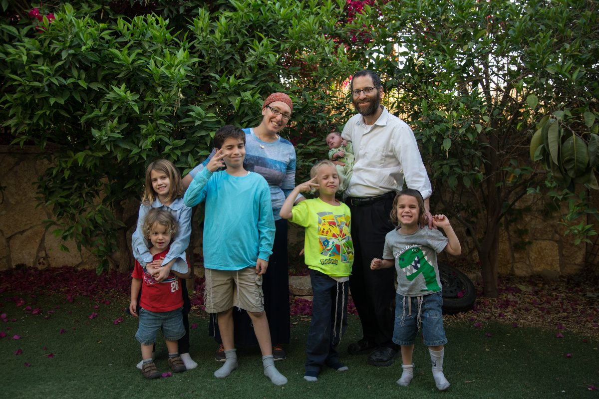 Lauren and Ira Somers in their backyard in Israel, with their children: From left, Uriel, 2; Riva, 9; Moshe, 10; Asher, 7; baby Ezra Dovid, born in April; and Yoel, 4.
