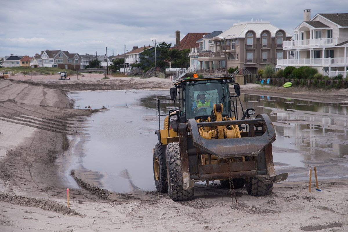 A construction vehicle purposed for moving dredging pipes backs into a pool of water at the beach in Margate.