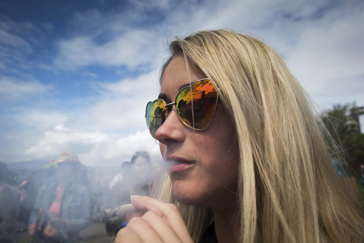 A woman smokes a joint during the annual 4/20 cannabis culture celebration at Sunset Beach in Vancouver, British Columbia, on  April 20.
