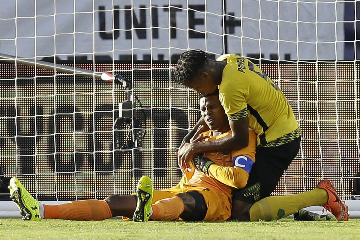 Jamaica goalkeeper Andre Blake, bottom, is consoled by Alvas Powell after being injured during the first half of the Gold Cup final soccer match against the United States in Santa Clara, Calif.