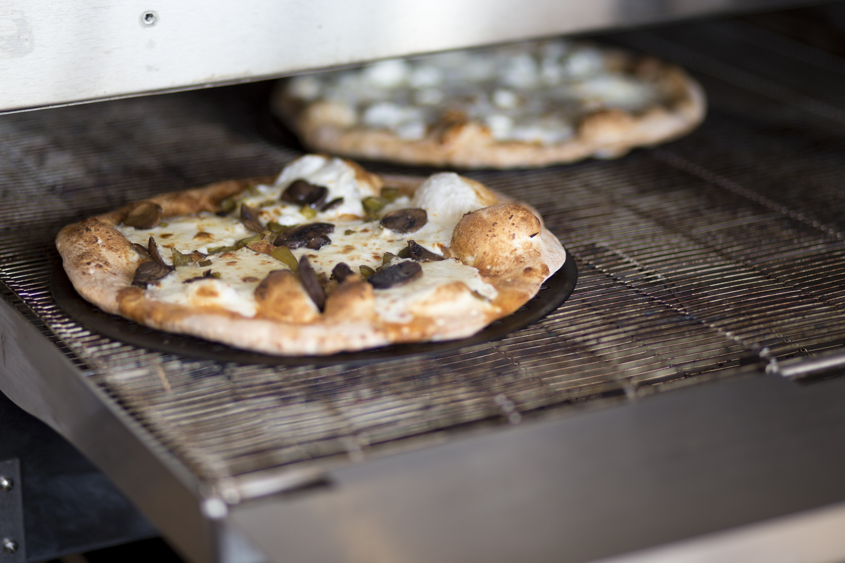 A pizza comes out of the oven at Snap Custom Pizza in Conshohocken Wednesday, July 26, 2017. Snap opened its sixth location July 25. ( MARGO REED / Staff Photographer )