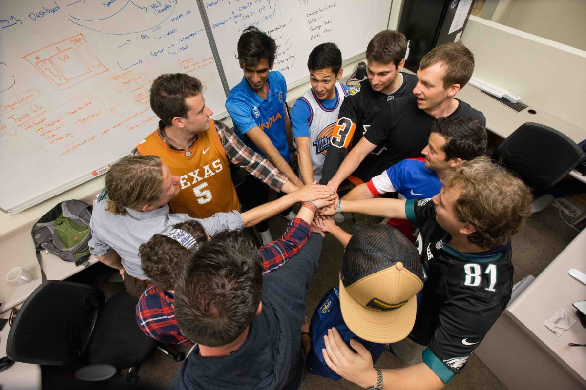 Evan Brandoff, second from top left (orange shirt), and Zubin Teherani, fourth from left (short sleeved blue T-shirt with white tank over top), lead an employee team huddle at their offices.