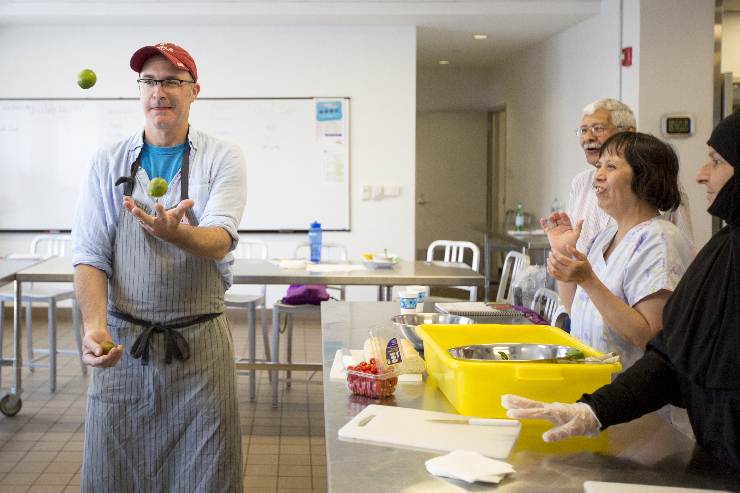 Jameson O´Donnell, a chef instructor, juggles limes before starting the ESL cooking class at the culinary learning center in the Free Library on Vine Street Wednesday, July 26, 2017. Immigrants from around the world sign up for the class to enhance their English skills through cooking and talking about food.